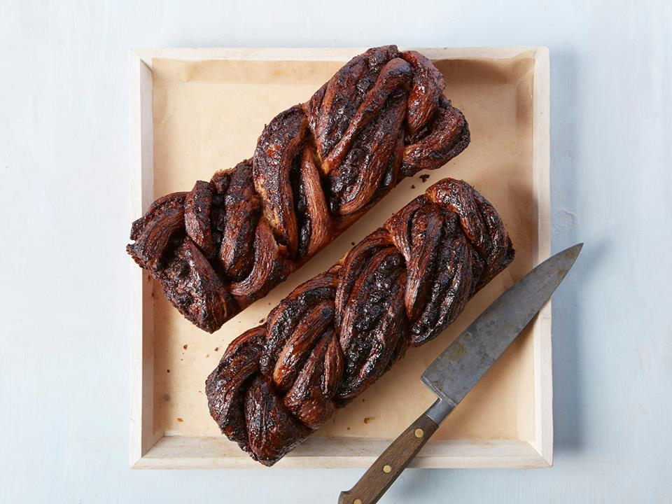 An overhead photo of two loaves of chocolate babka beside a cutting knife