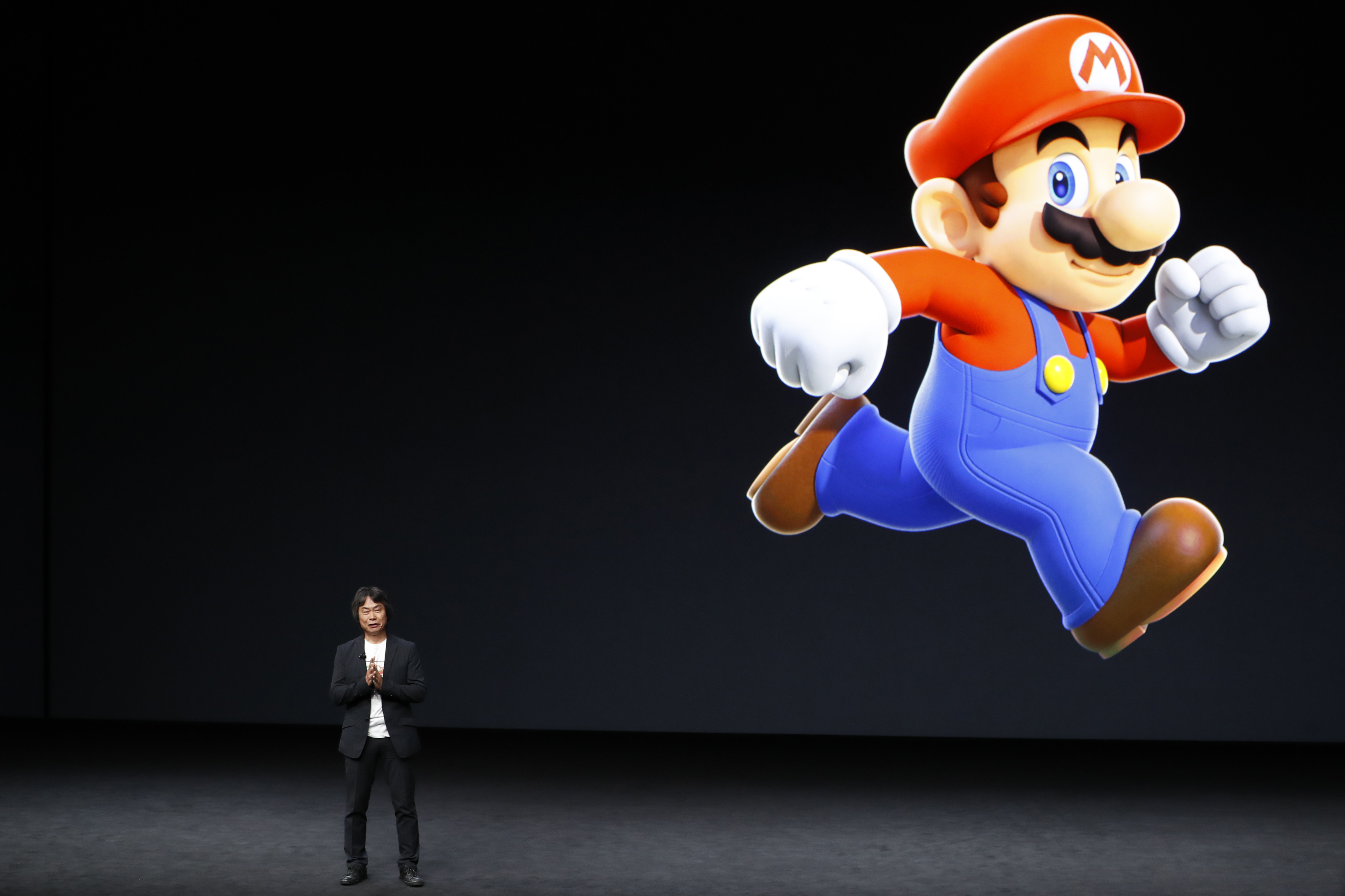 Shigeru Miyamoto speaks on a stage with a giant Mario running in the backround