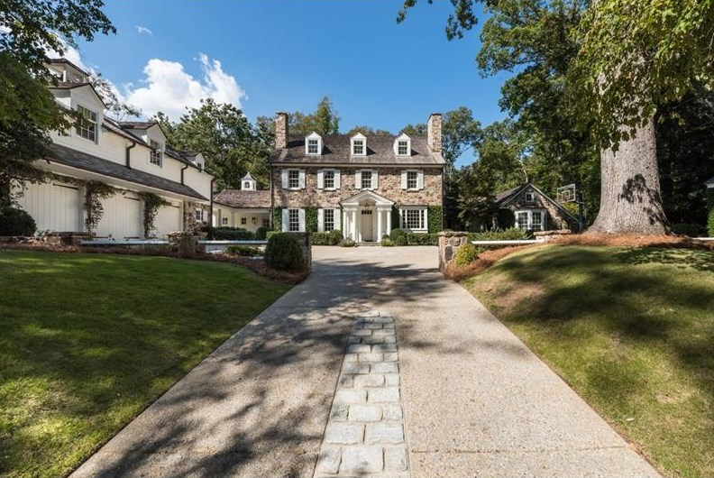 Driveway leading to three-story stone house.
