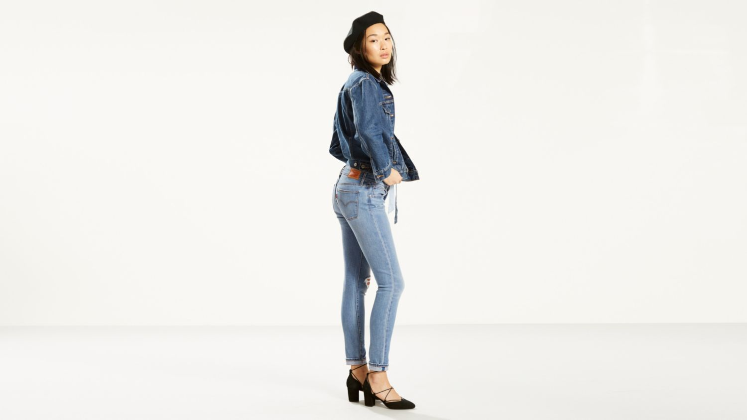 A model wearing a denim jacket and jeans