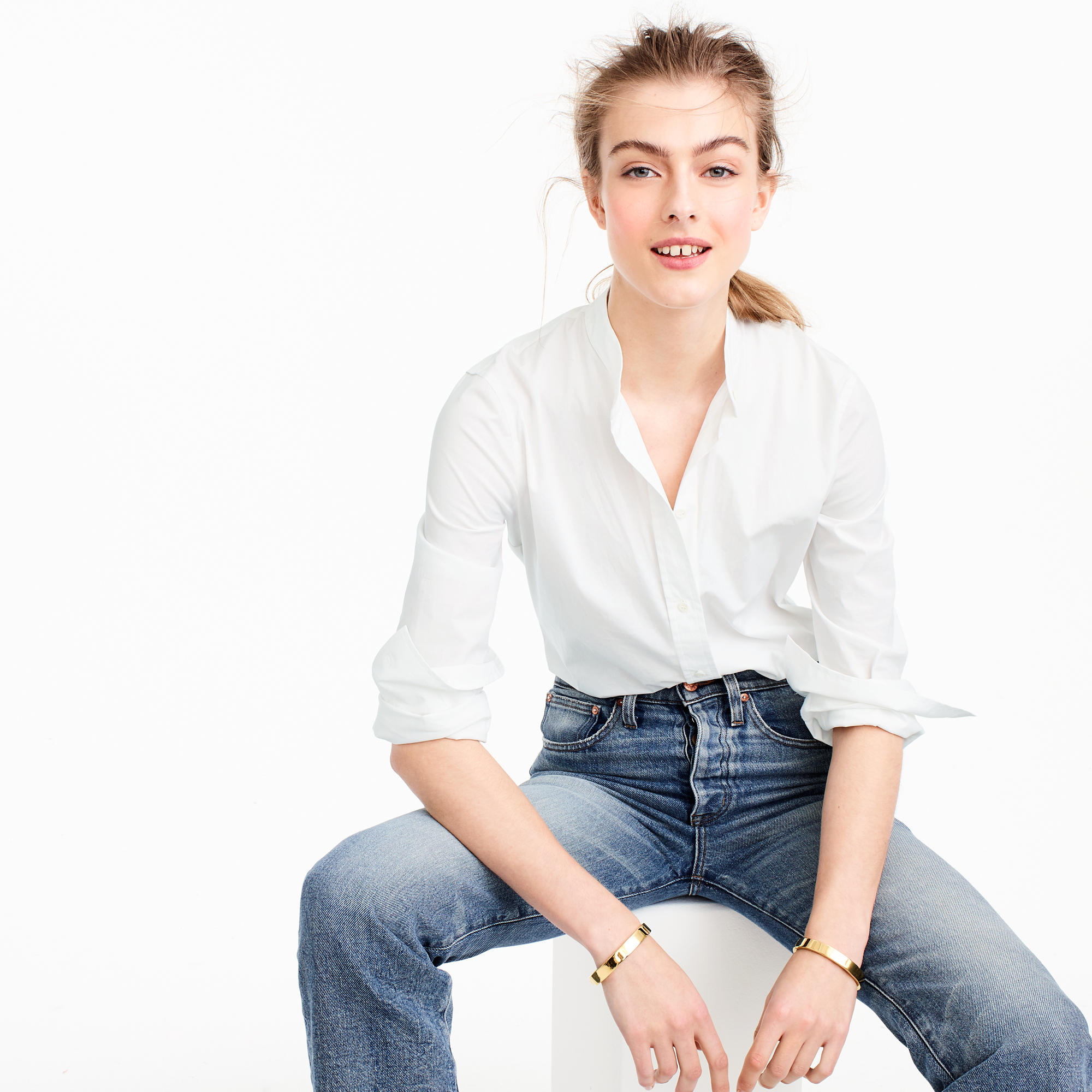A woman in white button-down and jeans