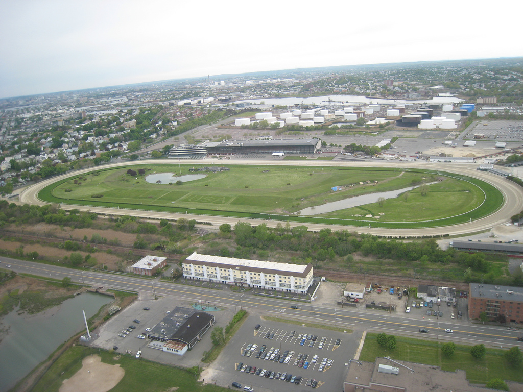 An aerial view of a large park space. There are buildings on the perimeter of the park space.
