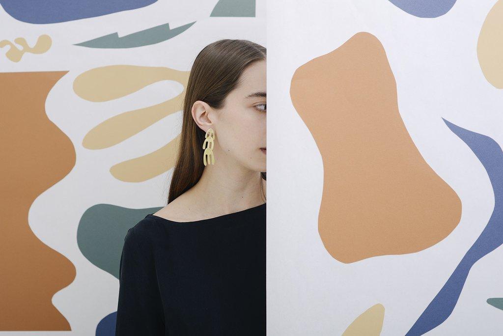 A model wearing geometric earrings, standing behind a geometric facade