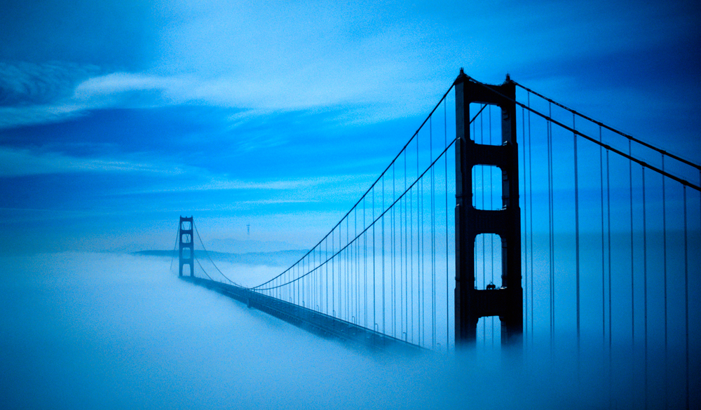 The towers of a suspension bridge, surrounded by eerie bluish fog at night.