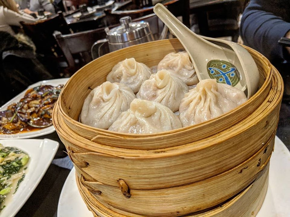 Six soup dumplings in a bamboo steamer basket with large soup spoons tucked in next to the dumplings. Several other dishes of food are visible in the background.