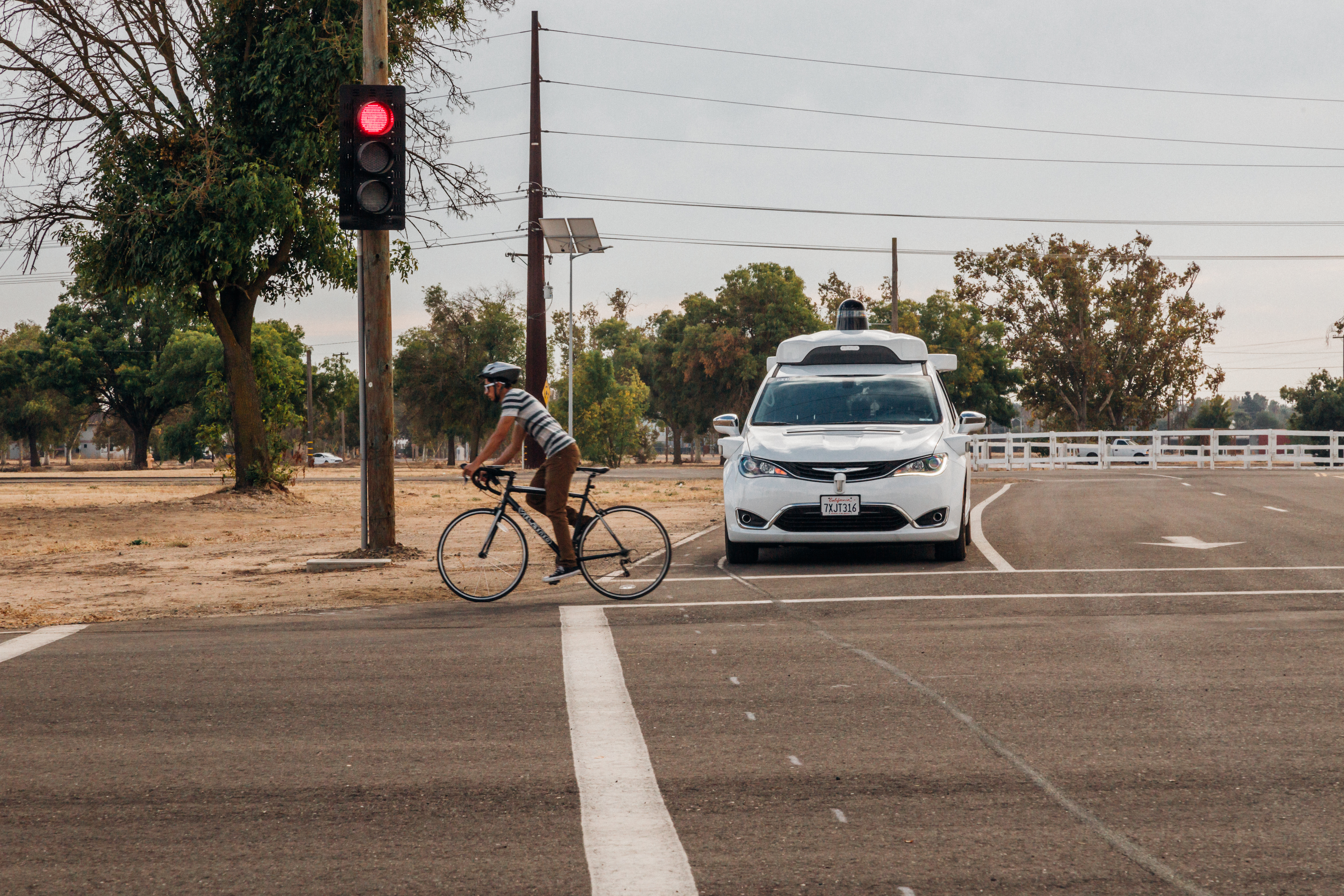 Alphabet's self-driving van waits for a cyclist to cross the road.