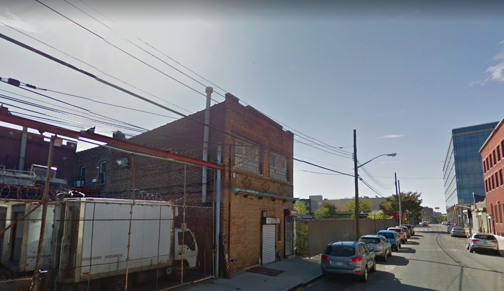Buildings and parked cars along a street in Jamaica, Queens.