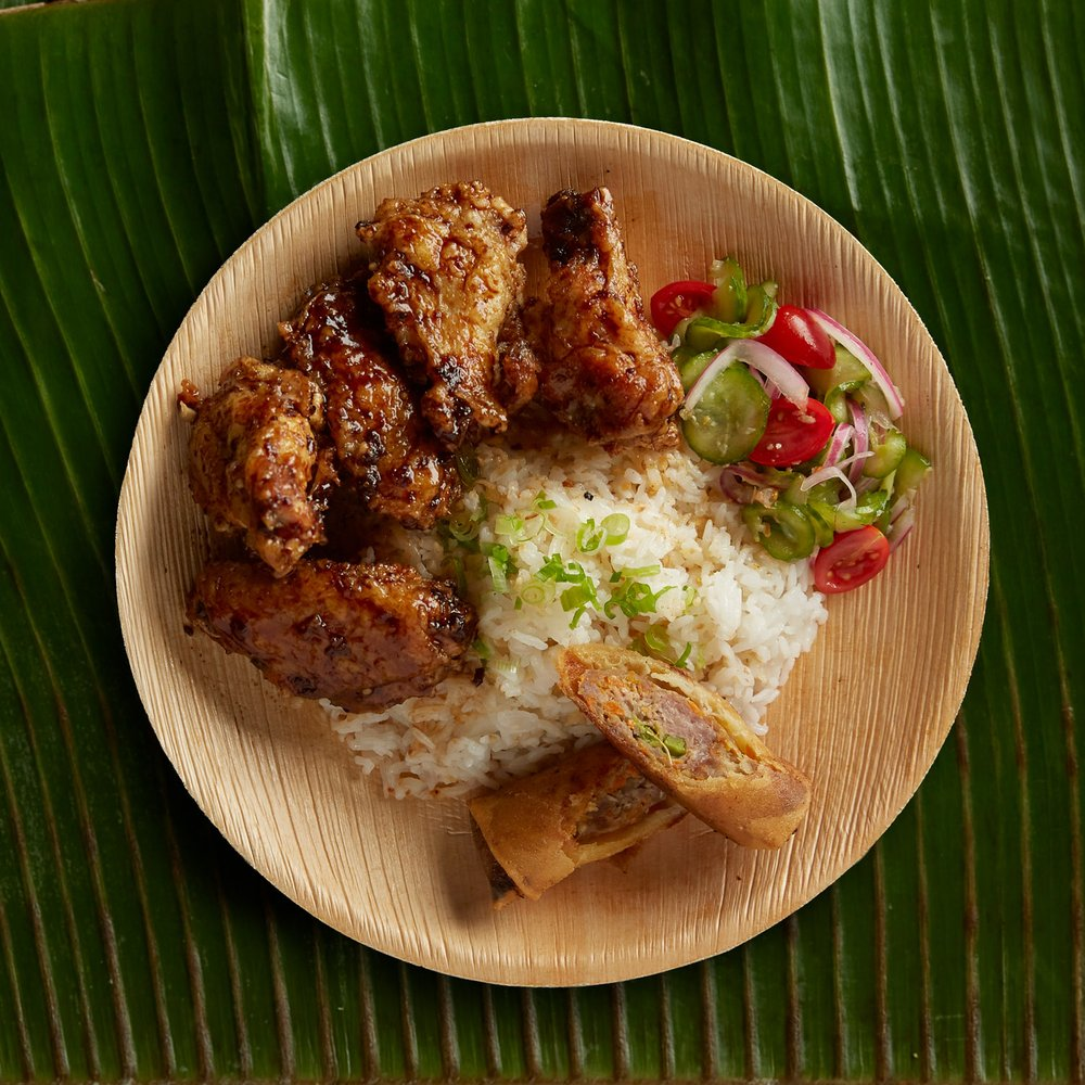 A platter of adobo fried chicken served with garlic fried rice and other fixings.