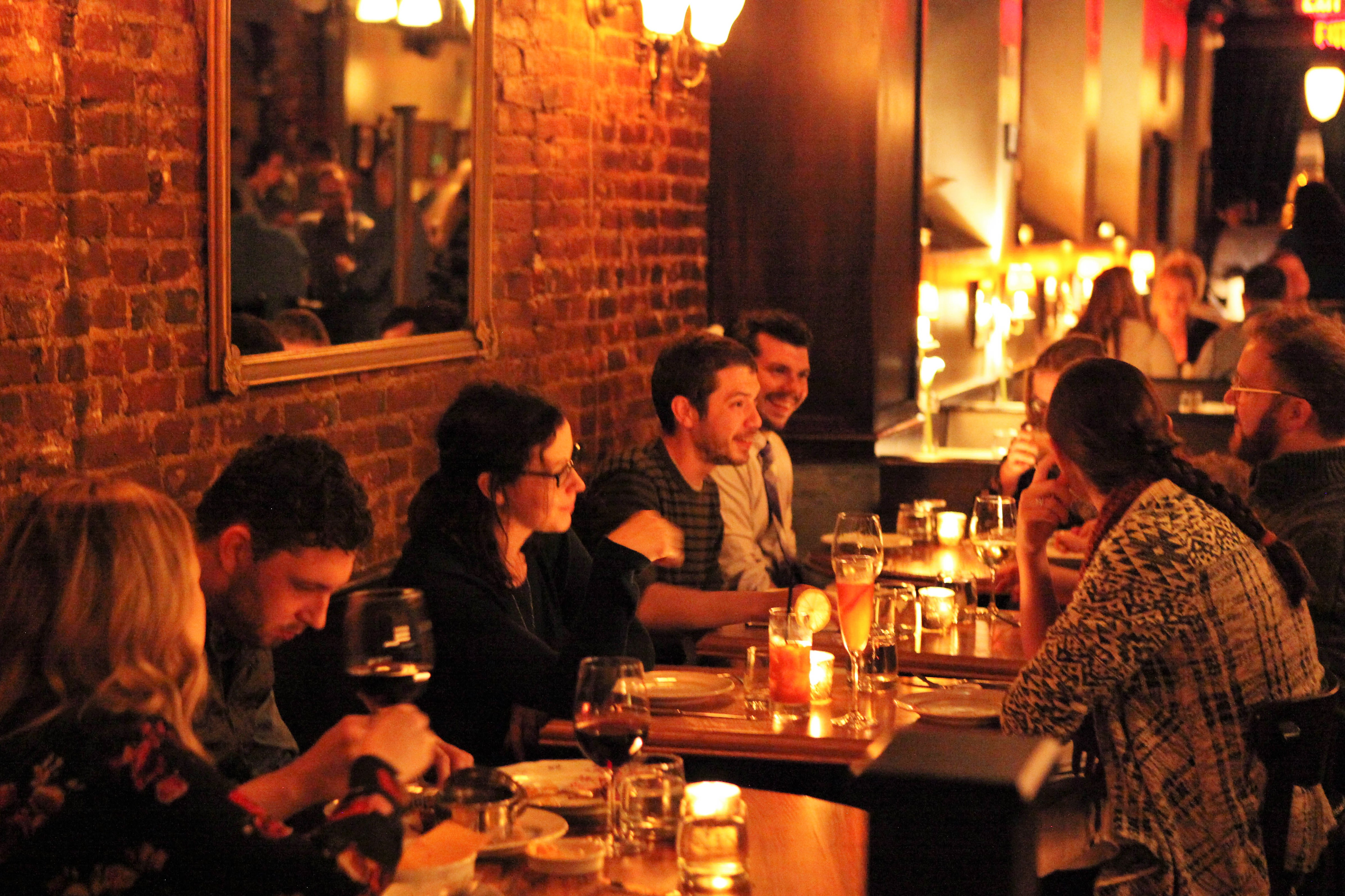 diners at tables in a candlelit restaurant with a brick wall