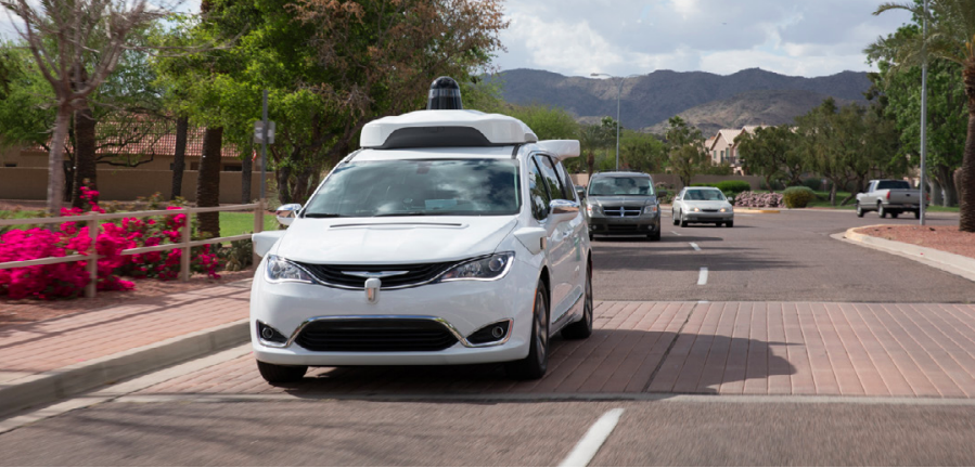 Waymo's self-driving Chrysler Pacifica drives on a road with other cars in the background.