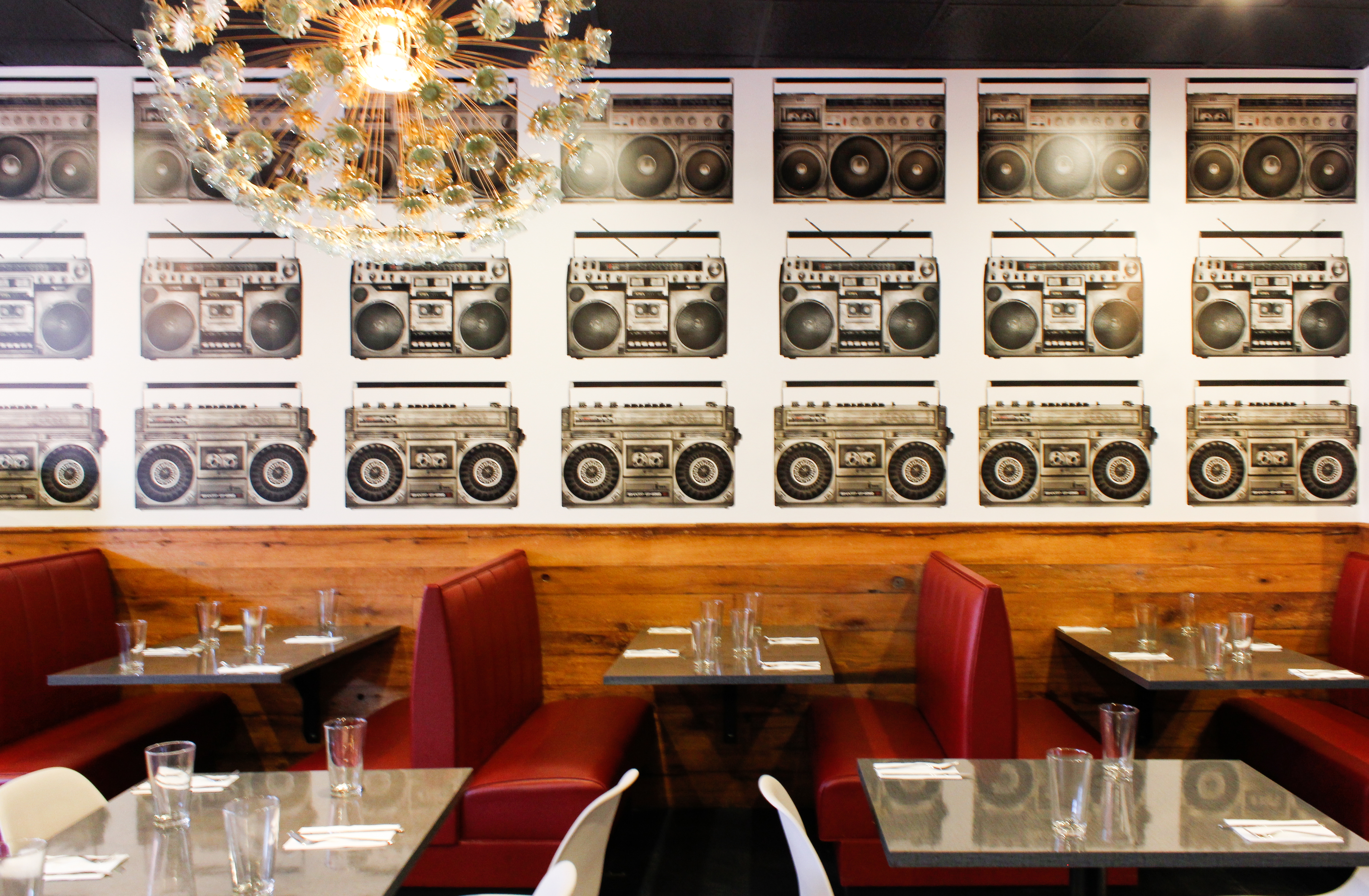 An interior photo of part of Stoked's original Brookline location, including red booths, black-and-white wallpaper covered with a bold boombox pattern, and a funky light fixture.