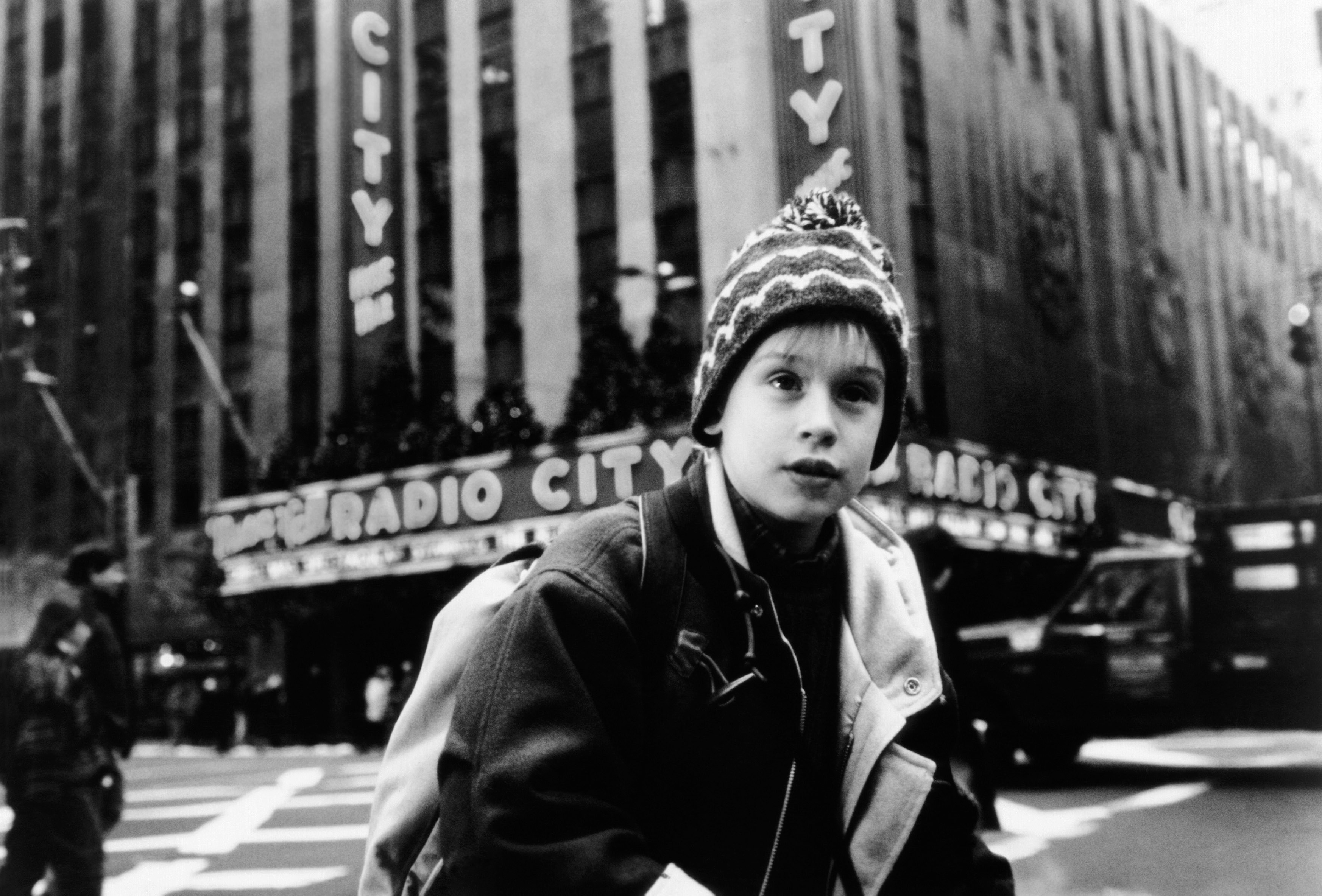 A boy in outdoor winter clothing crosses a city street. The building in the background has a sign that reads Radio City.