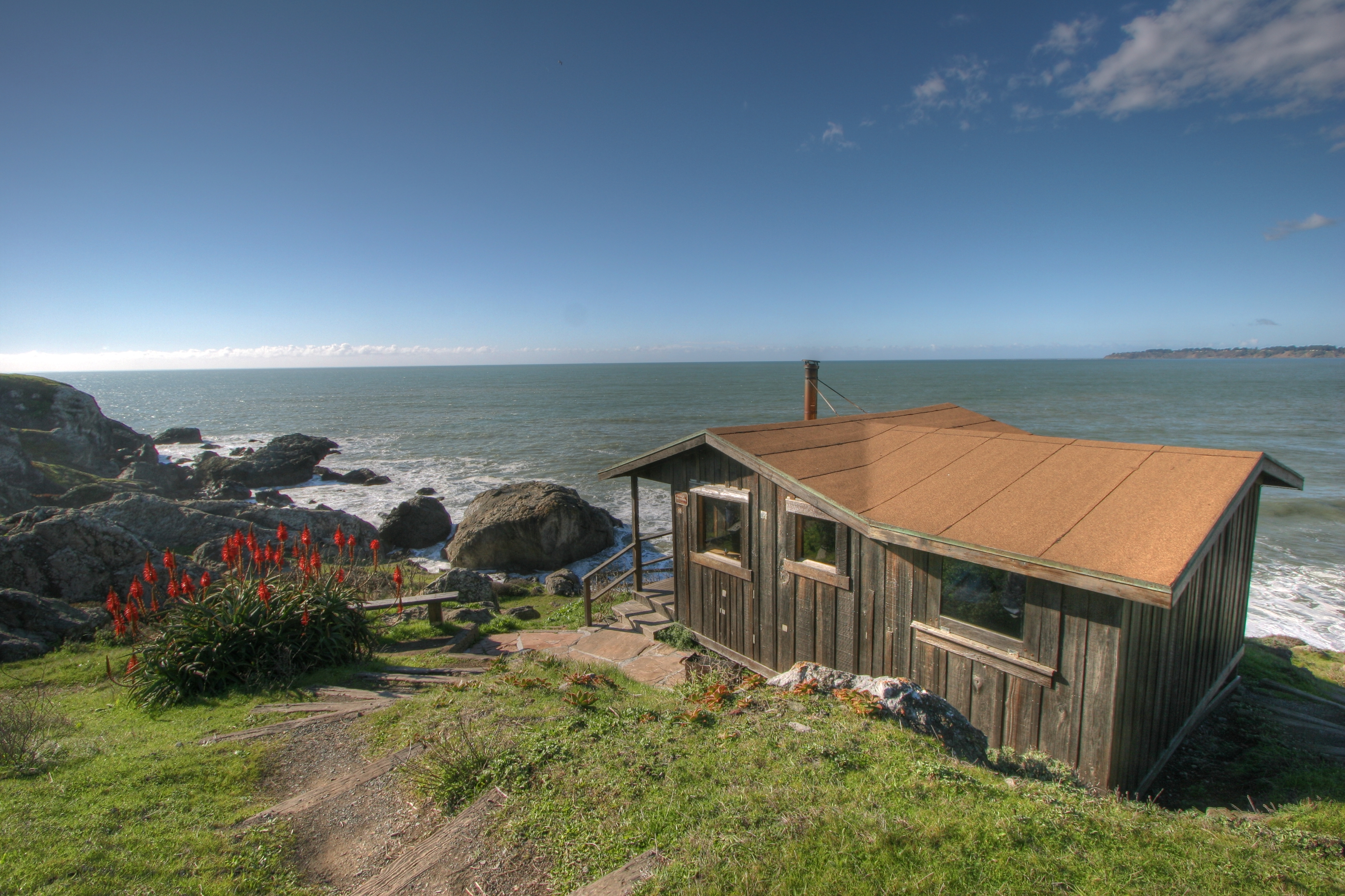 A wooden cabin on the edge of a cliff. There is a body of water and a beach in the distance.