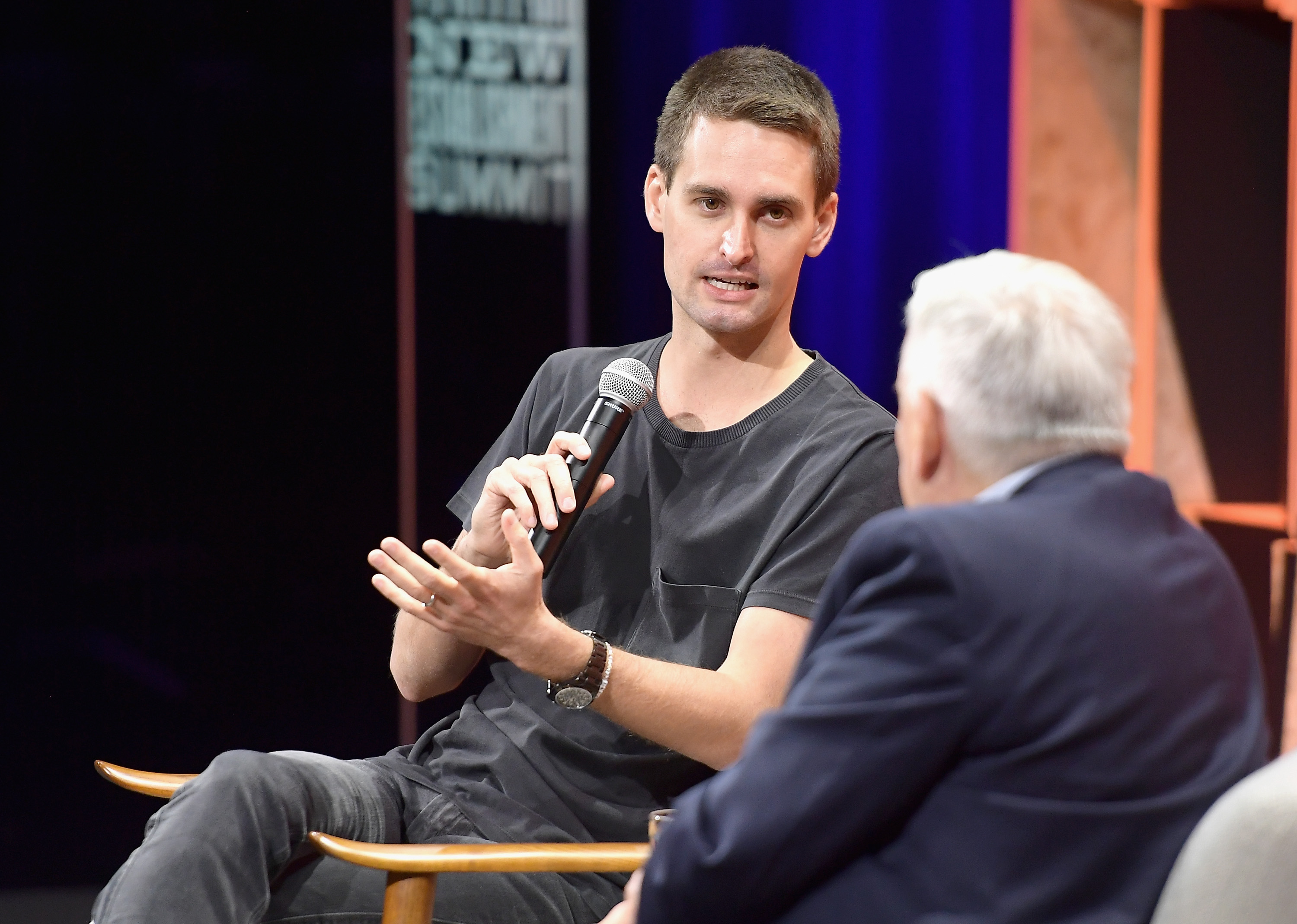 Snap CEO Evan Spiegel onstage holding a microphone