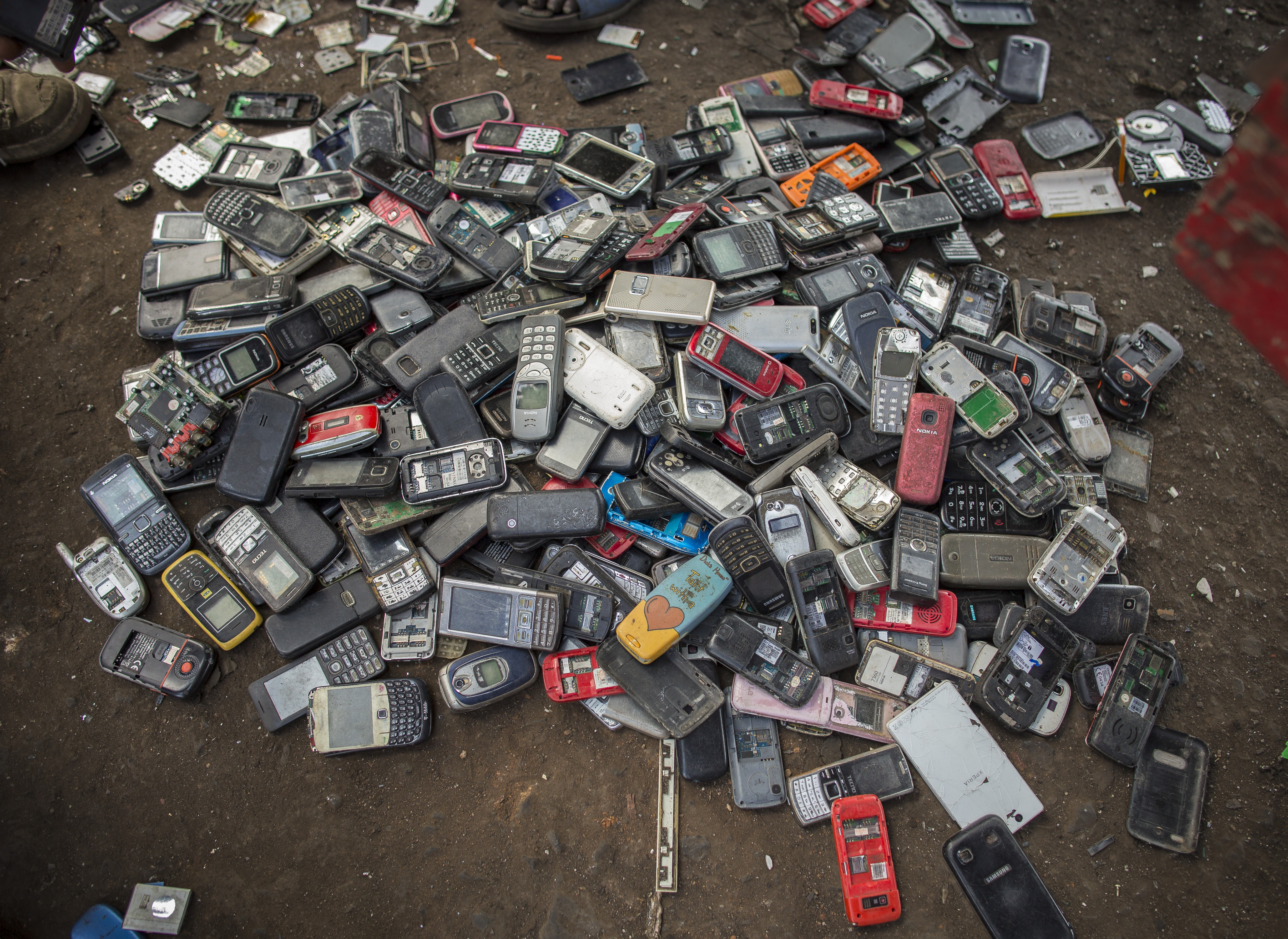 Used electronics, mostly old smartphones, piled on the ground