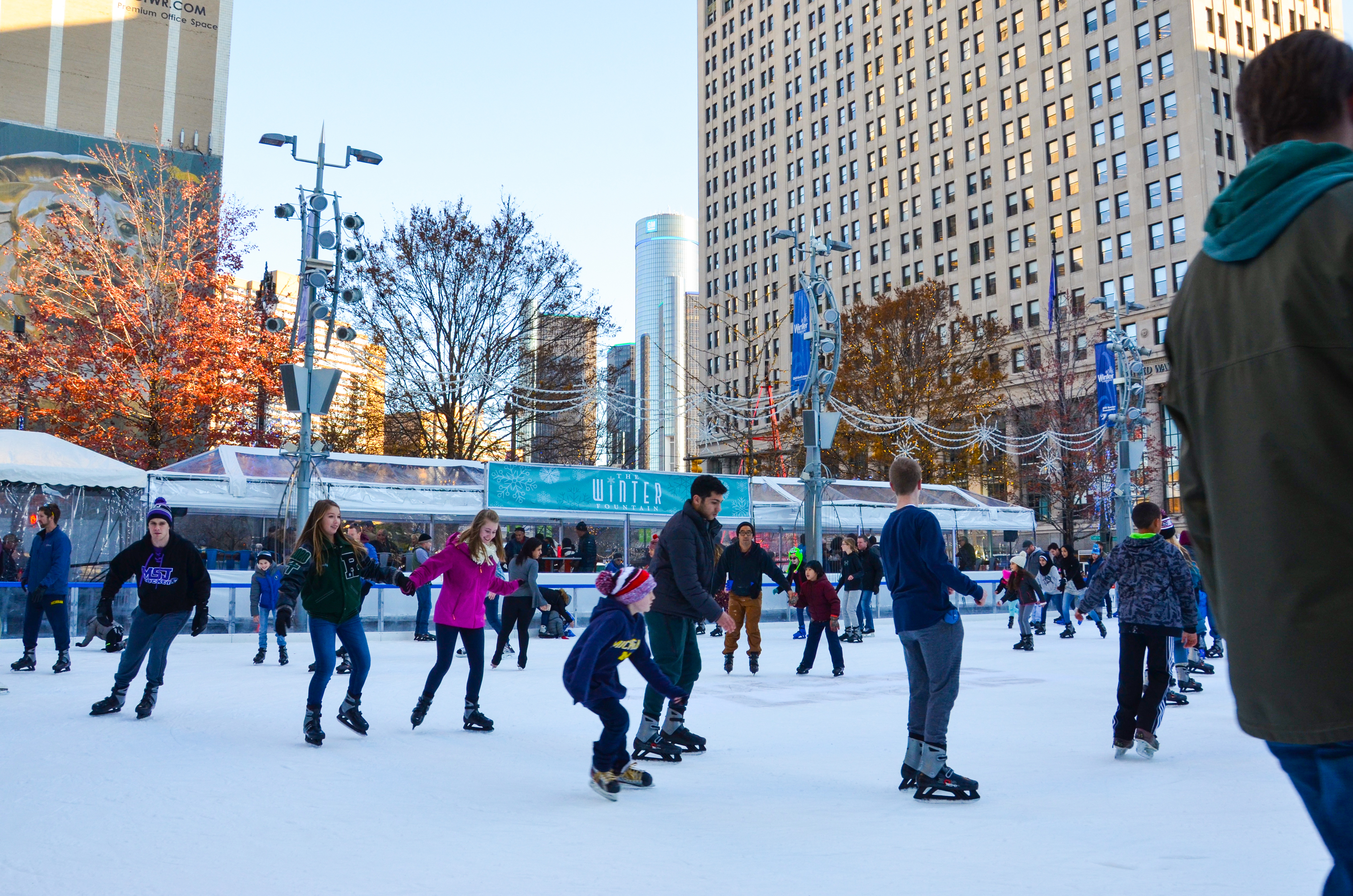 Kids with some adults at an ice rink surrounded by skyscrapers.