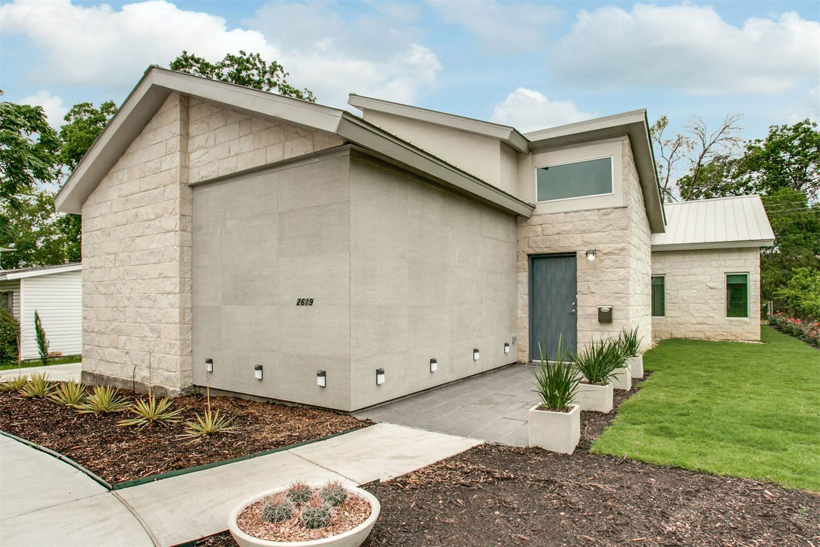 Contemporary home with stone and tile facade.