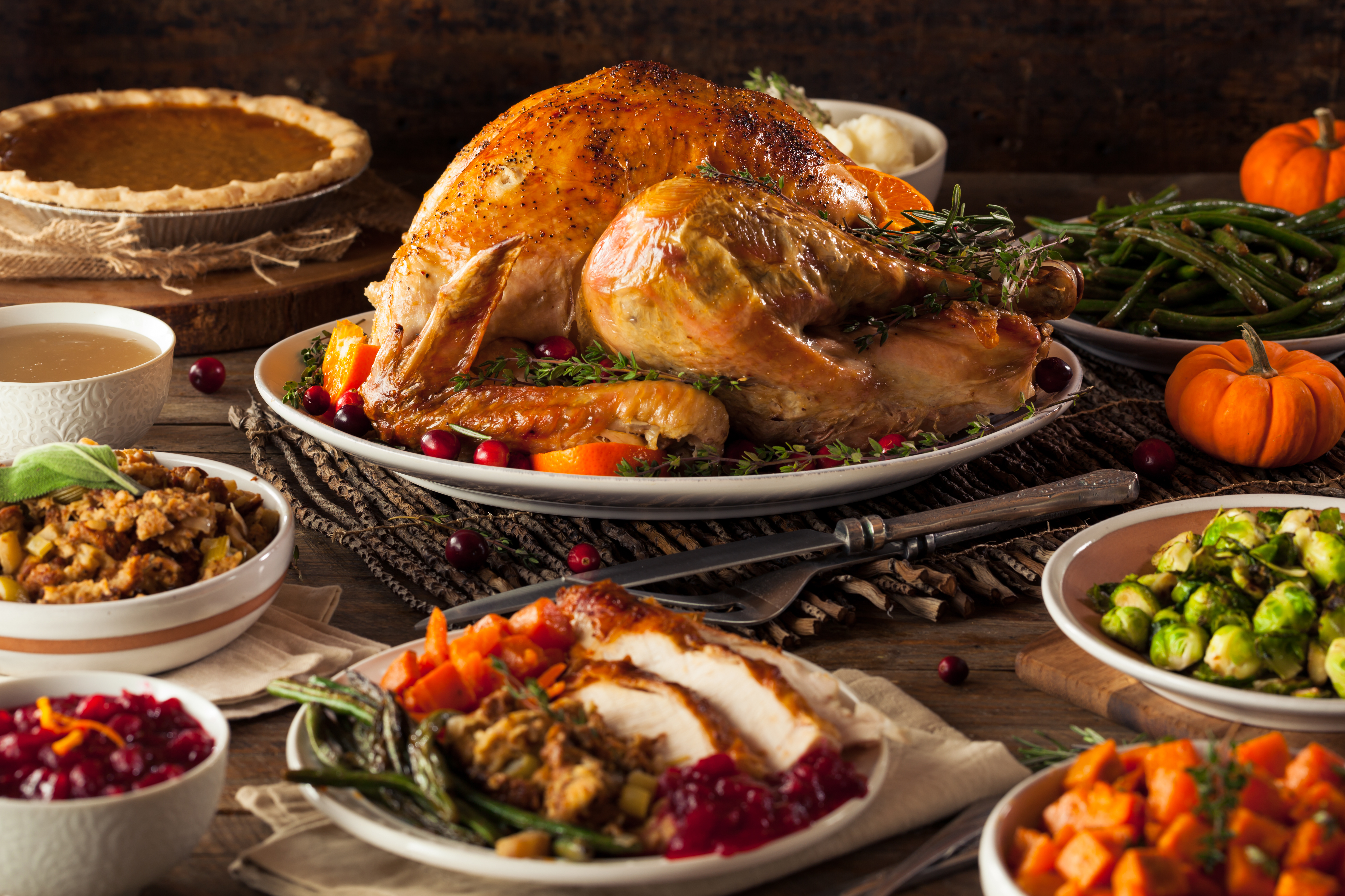 A thanksgiving spread covers a table, large roasted turkey on a white platter in the center, surrounded by sides and pumpkin decor
