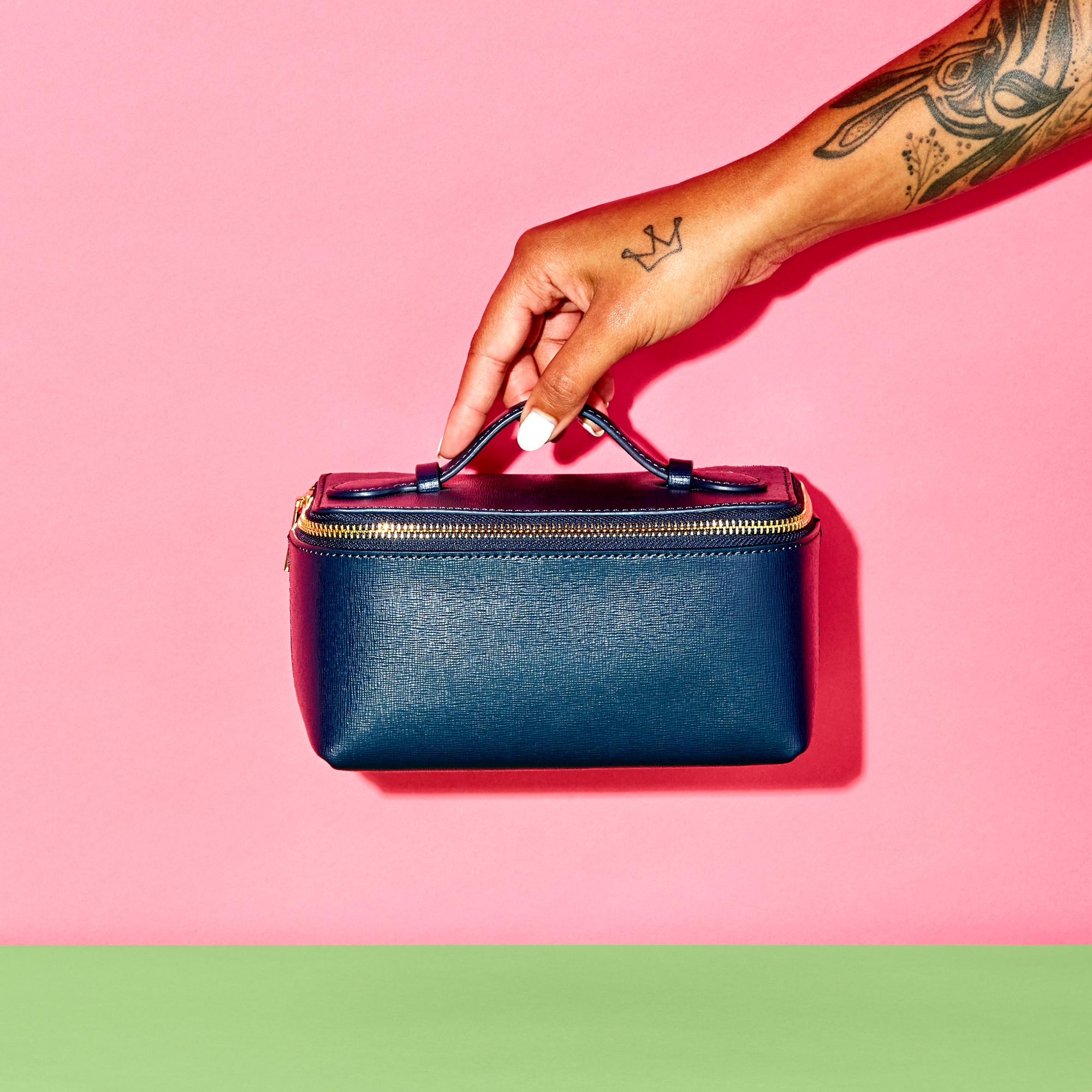 A hand holding a small blue leather purse.