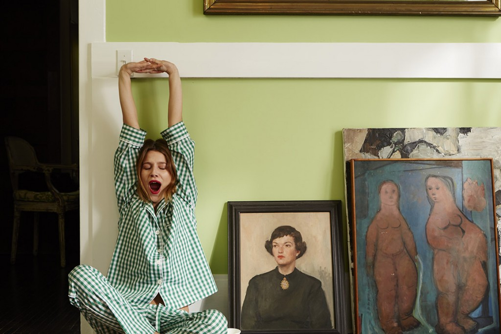 A woman in striped PJs yawns and stretches