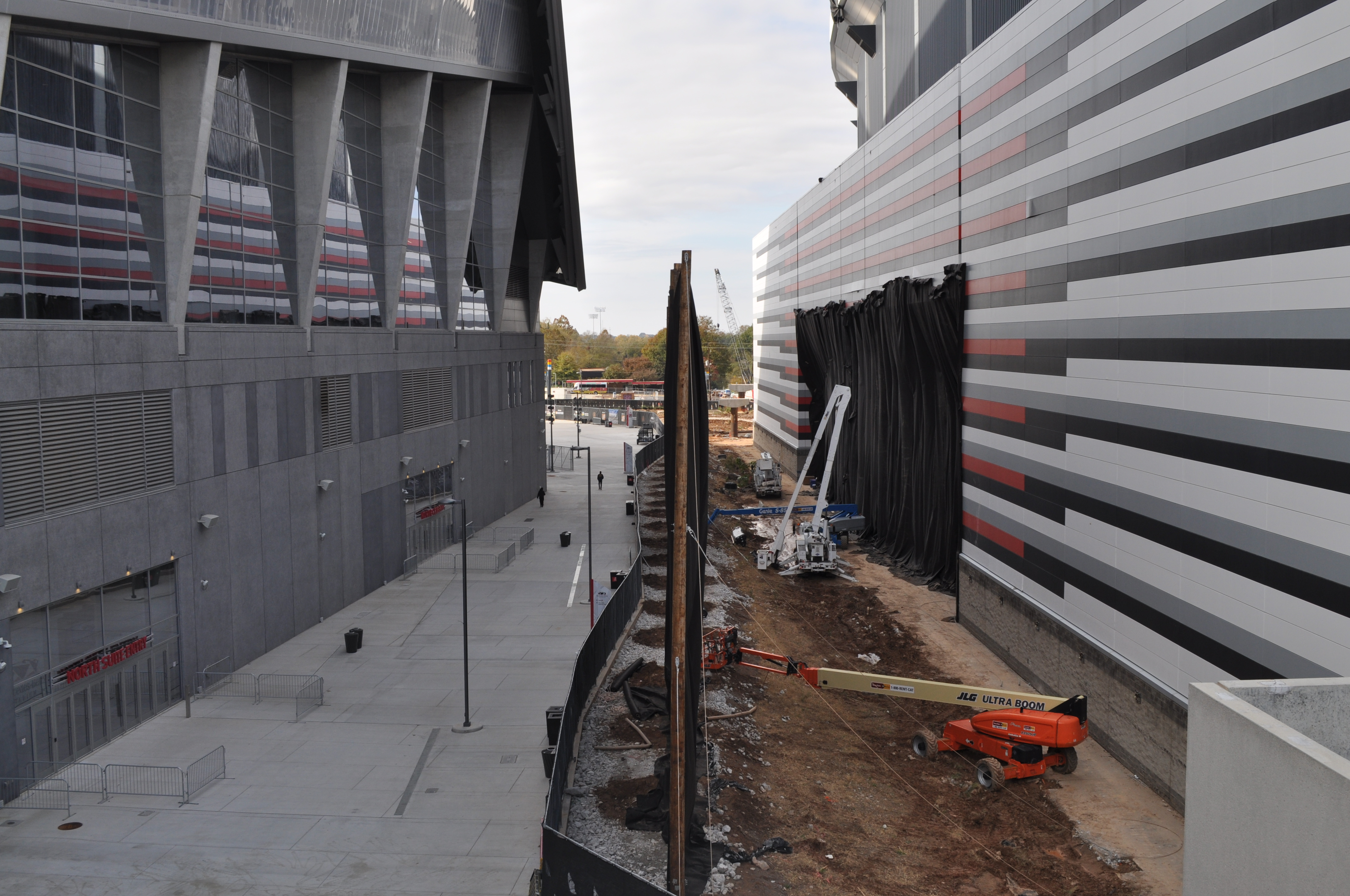 A tall fabric wall, strung between telephone poles, being built in the 30-foot gulf between the two stadiums.