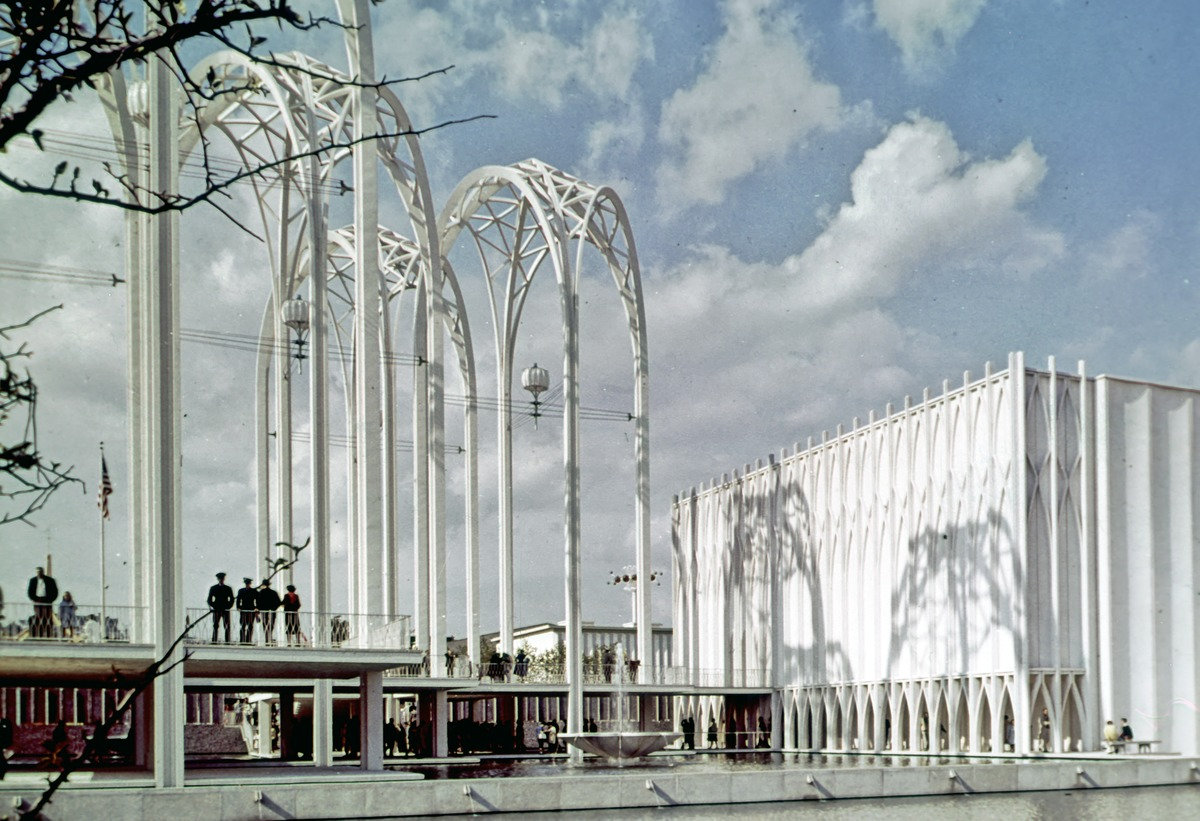 Three tall, white arches—three-dimensional structures with four legs each—tower in front of a lightly cloudy sky. A white building, shorter than the arches, is to the right.