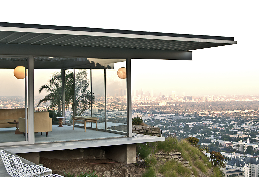 In the foreground is a house with a glass room that is situated on a cliff edge. The view in the distance is of a cityscape.