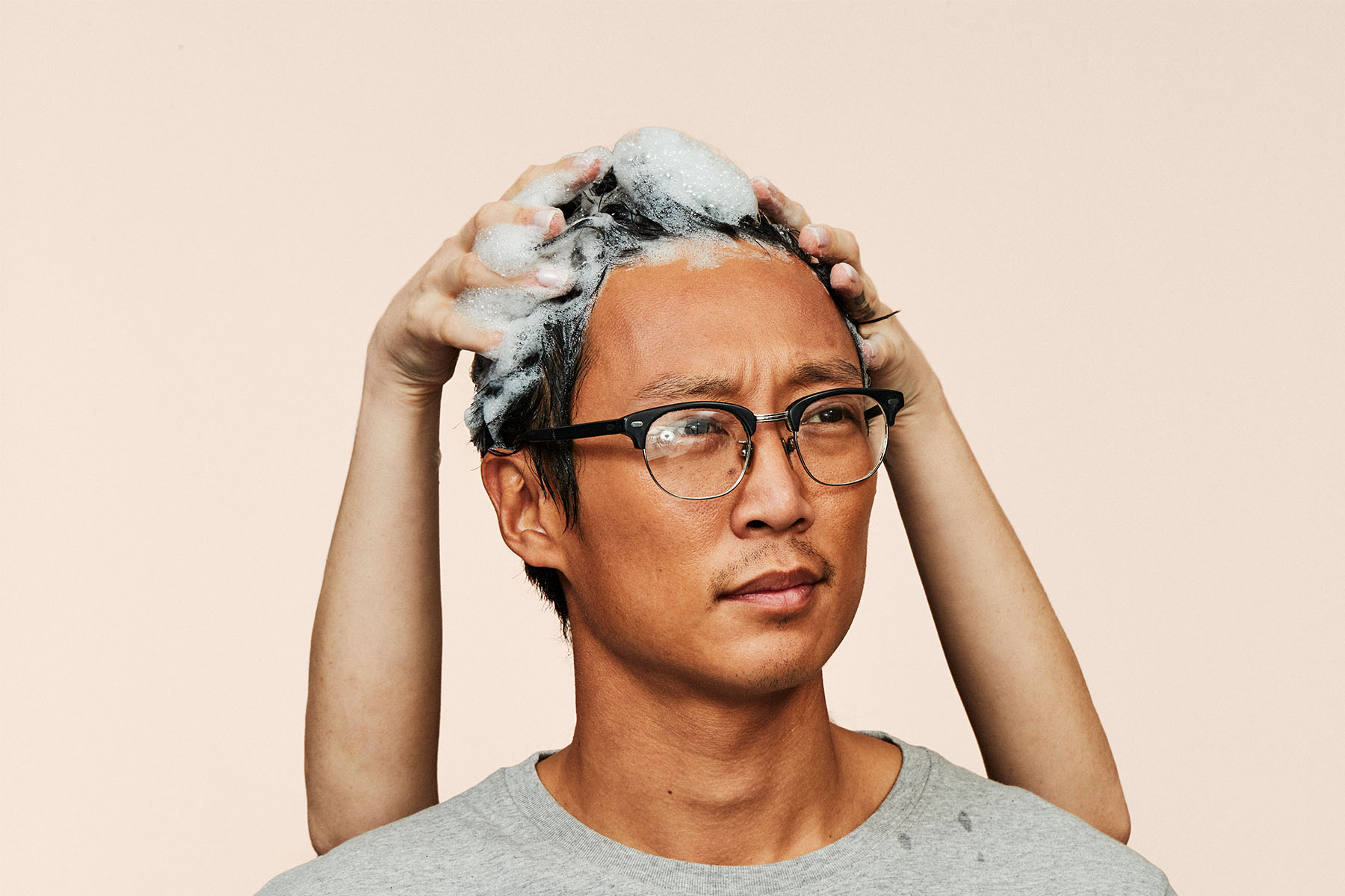 A man in glasses having his hair washed.