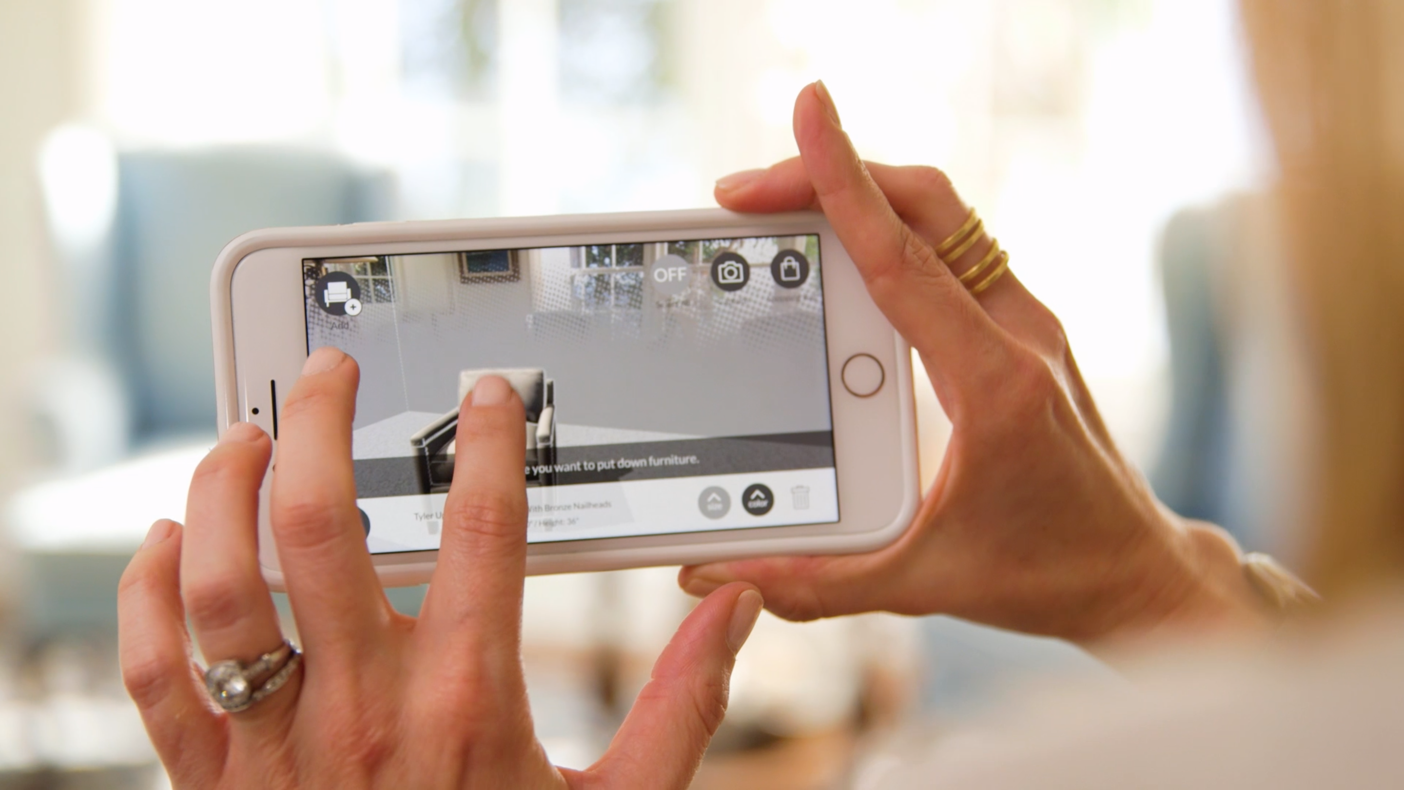 Two hands hold a mobile phone displaying an augmented reality app.