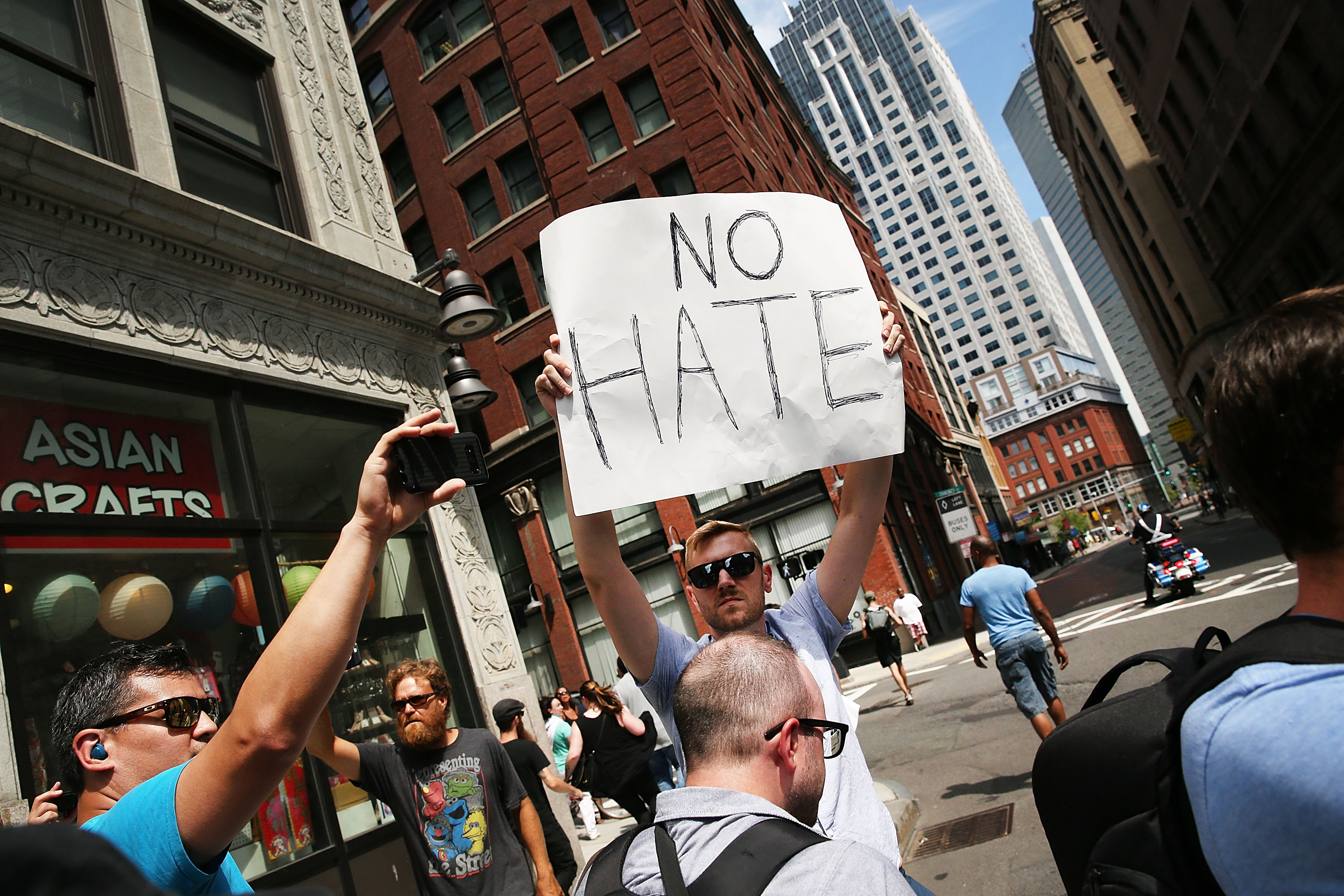 """A protester holds up a sign that reads, """"No hate."""""""