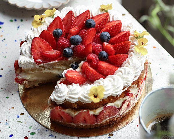 A round cake layered with white cream and strawberries, with a single slice cut out.