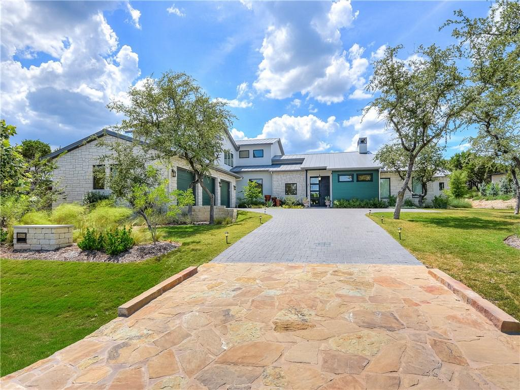 Long driveway with large contemporary at end, blue skies