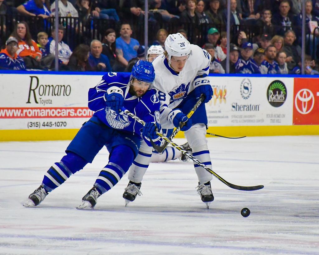 Syracuse Crunch Cory Conacher (89) and Toronto Marlies Kasperi Kapanen (28) skate after a loose puck in American Hockey League (AHL) Calder Cup Playoff action at the War Memorial Arena in Syracuse, New York on Friday, May 5, 2017. Syracuse won 3-1.