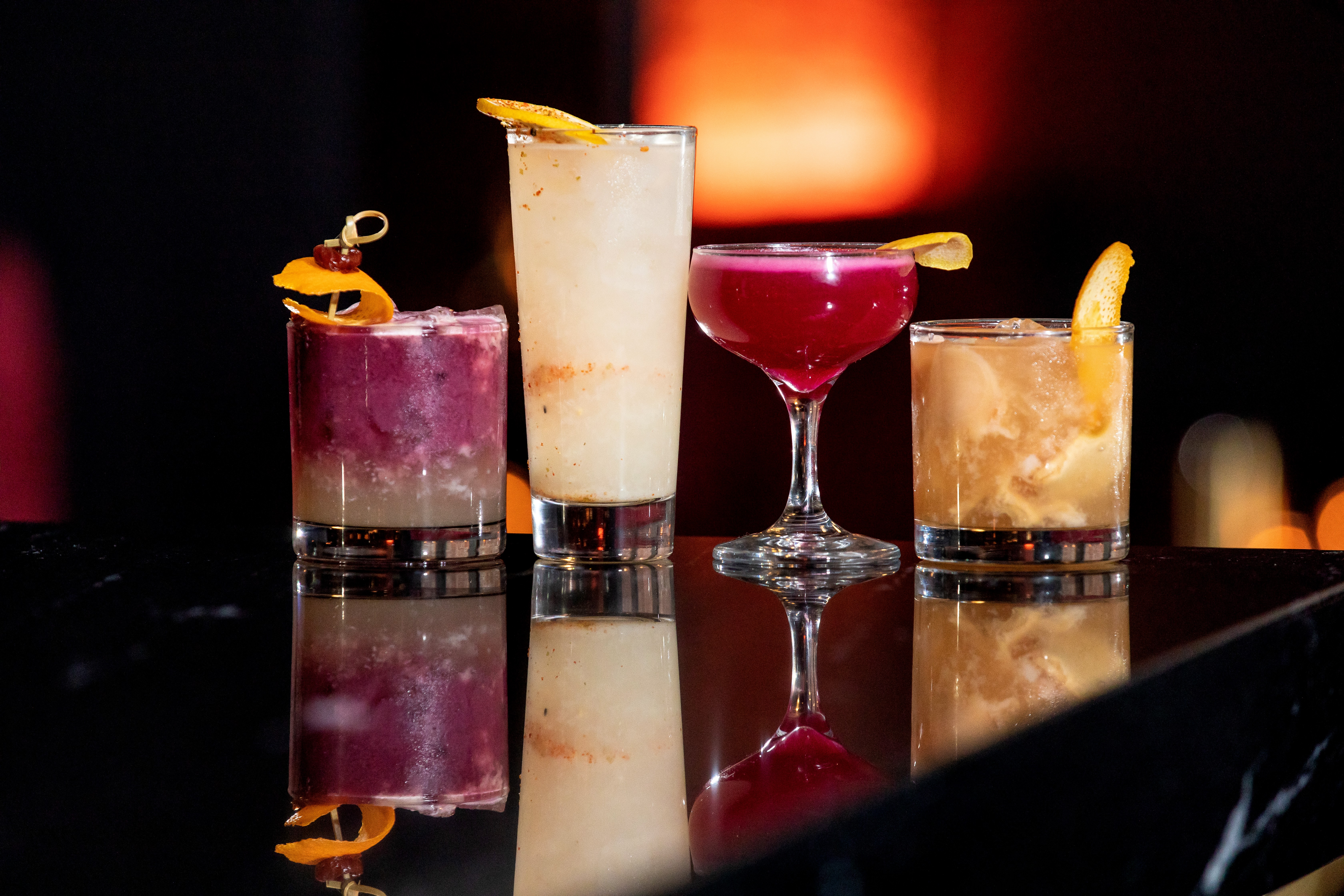 row of four colorful cocktails