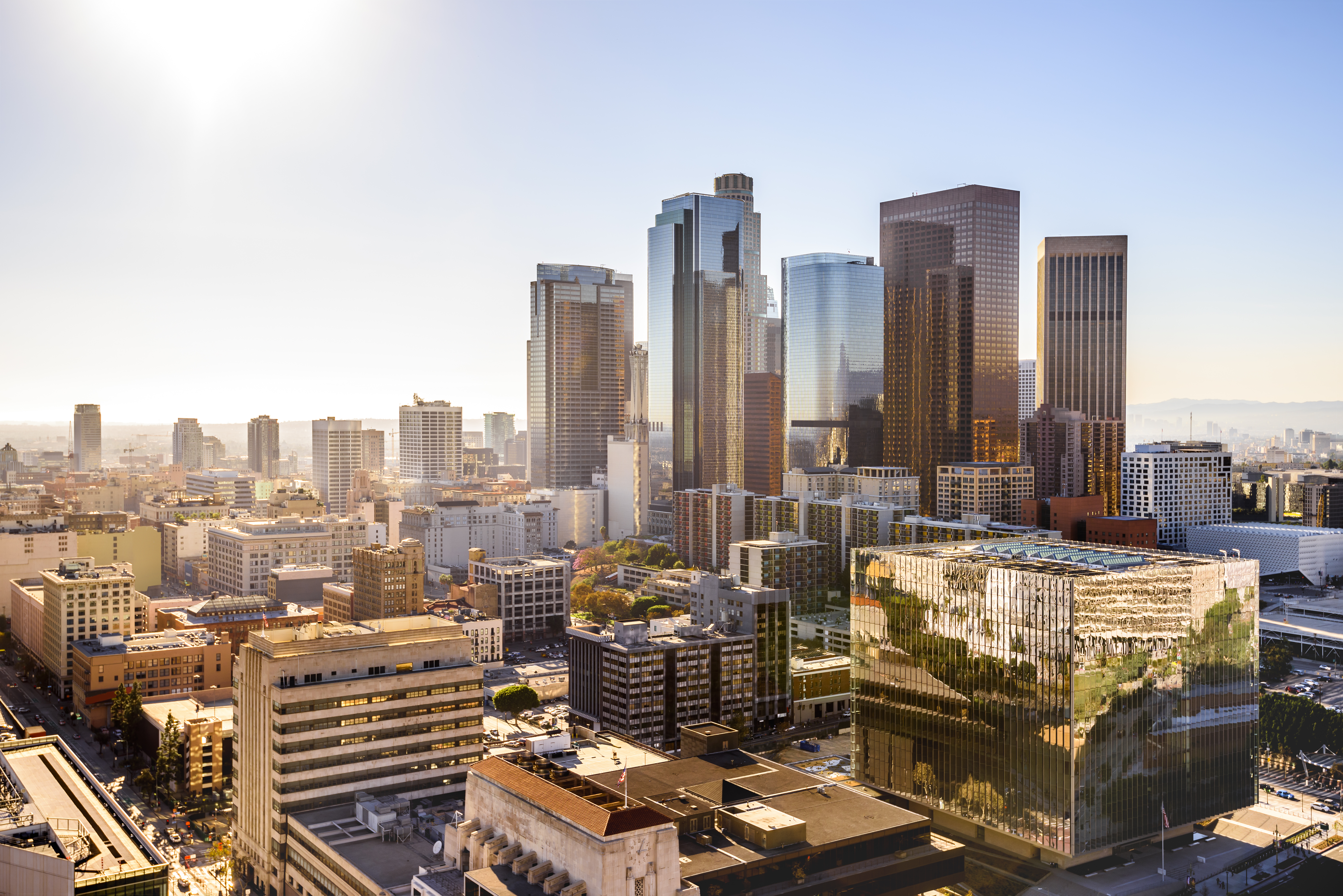 Aerial view of LA with sun gleaming off buildings
