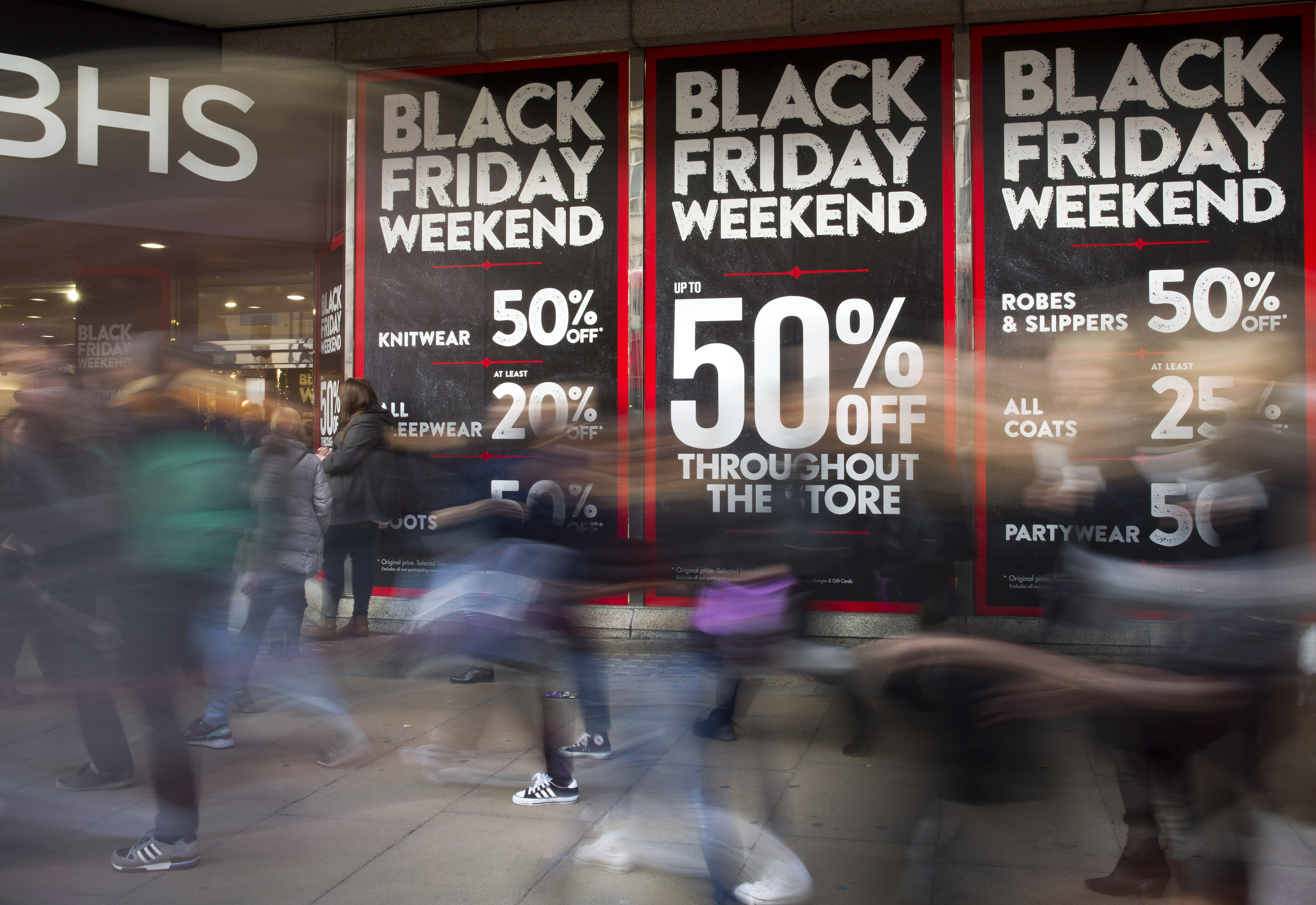 People zooming past a storefront advertising a Black Friday sale.