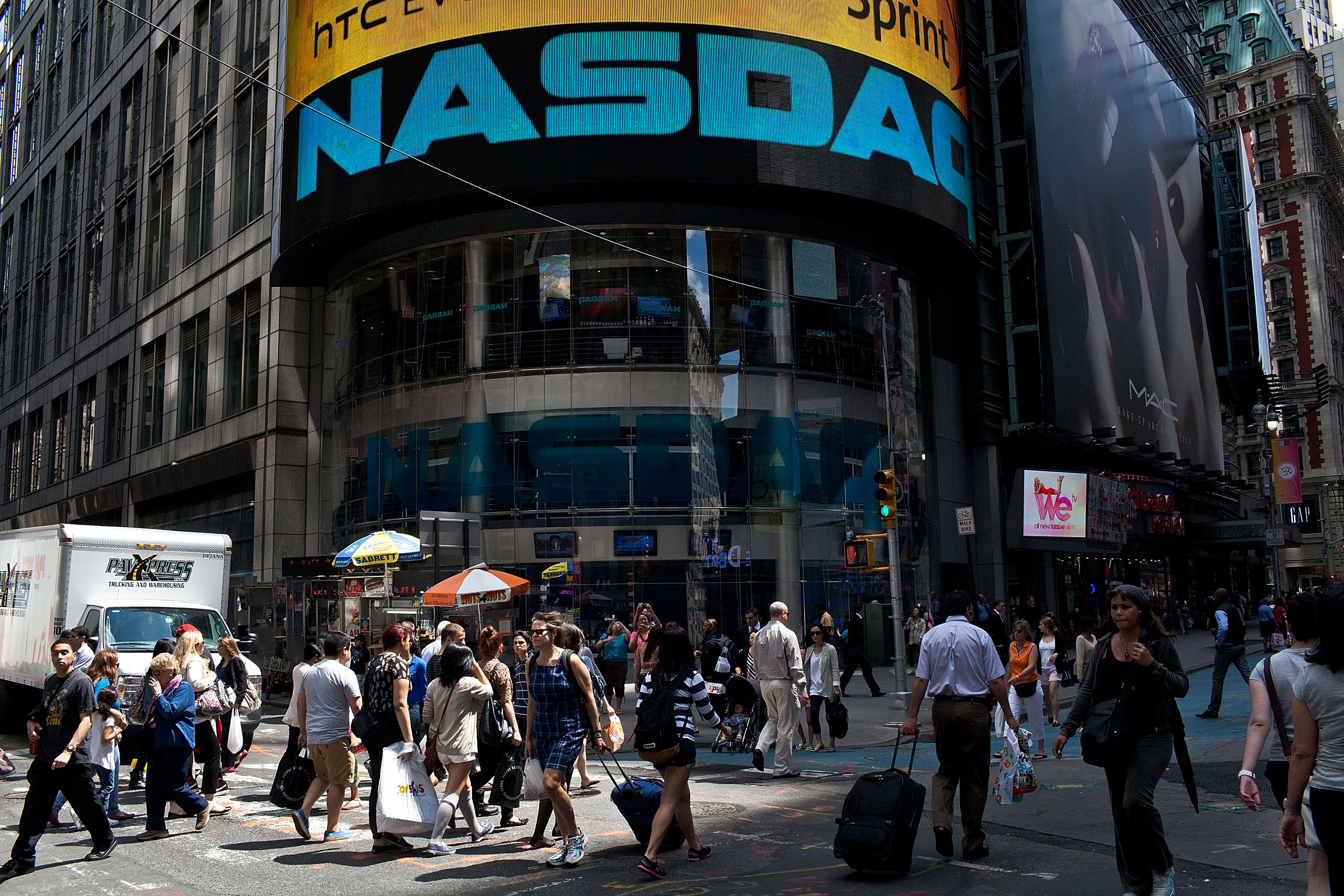 The entrance to the Nasdaq building with pedestrians walking by