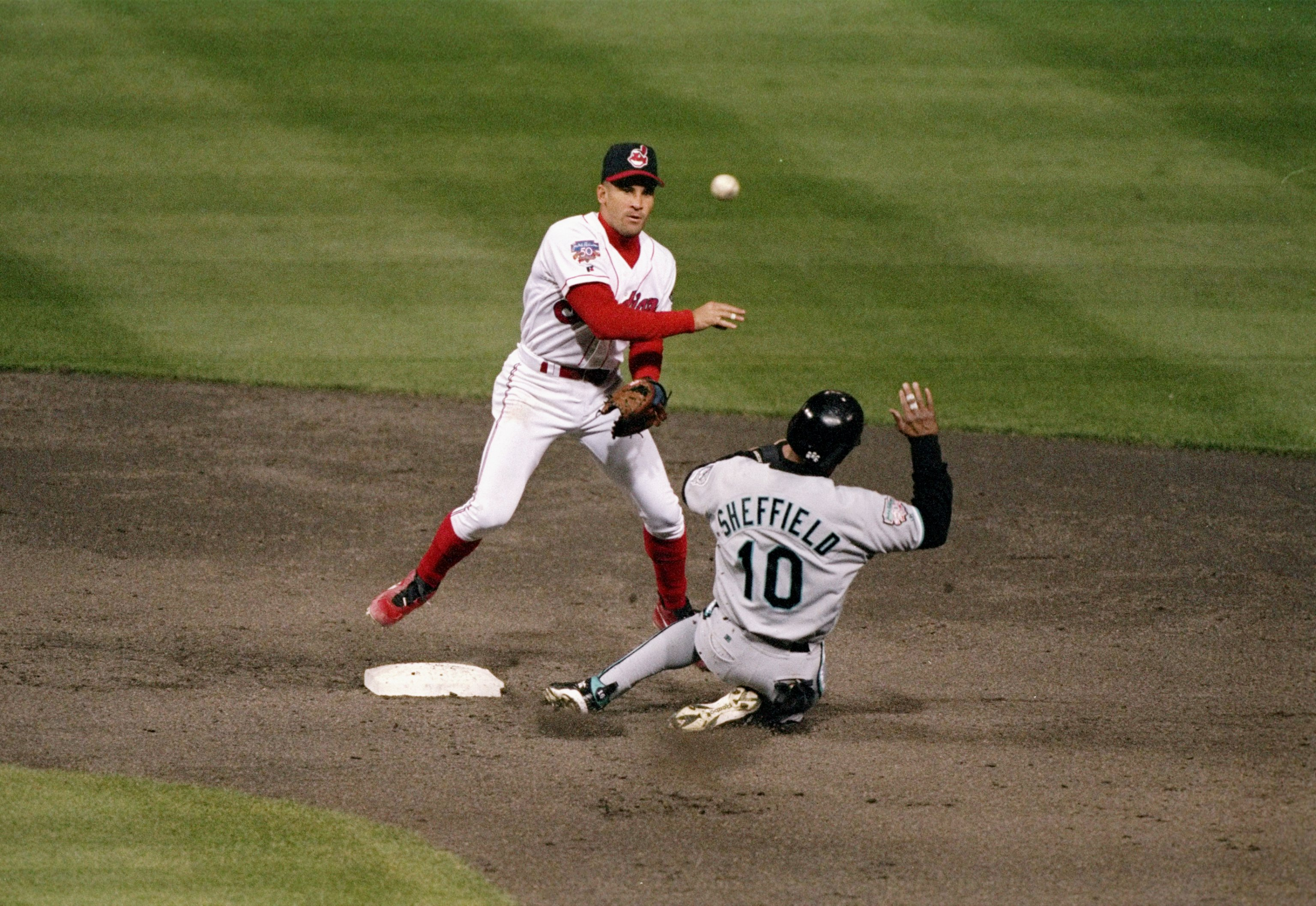 21 Oct 1997:  Shortstop Omar Vizquel of the Cleveland Indians (left) throws the ball for a double play as outfielder Gary Sheffield of the Florida Marlins slides toward the base during the third game of the World Series at Jacobs Field in Cleveland, Ohio.  The Marlins won the game 14-11. Mandatory Credit: Brian Bahr  /Allsport