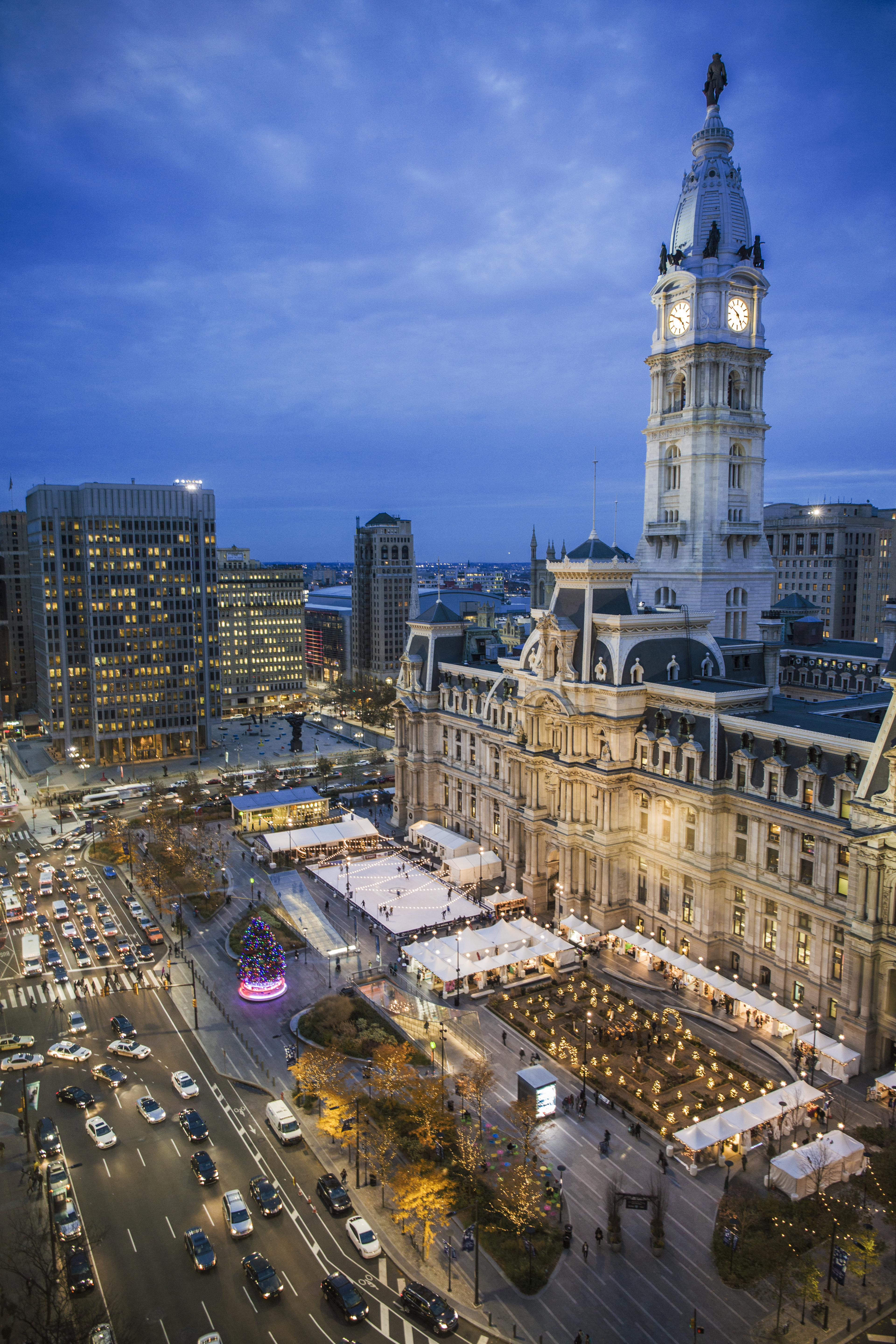 The exterior of Philadelphia City Hall. There is an ice rink in front of the building where people are ice skating.