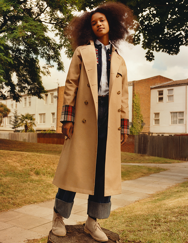 A model wearing a plaid accented trench coat from the JW Anderson x Uniqlo collaboration.