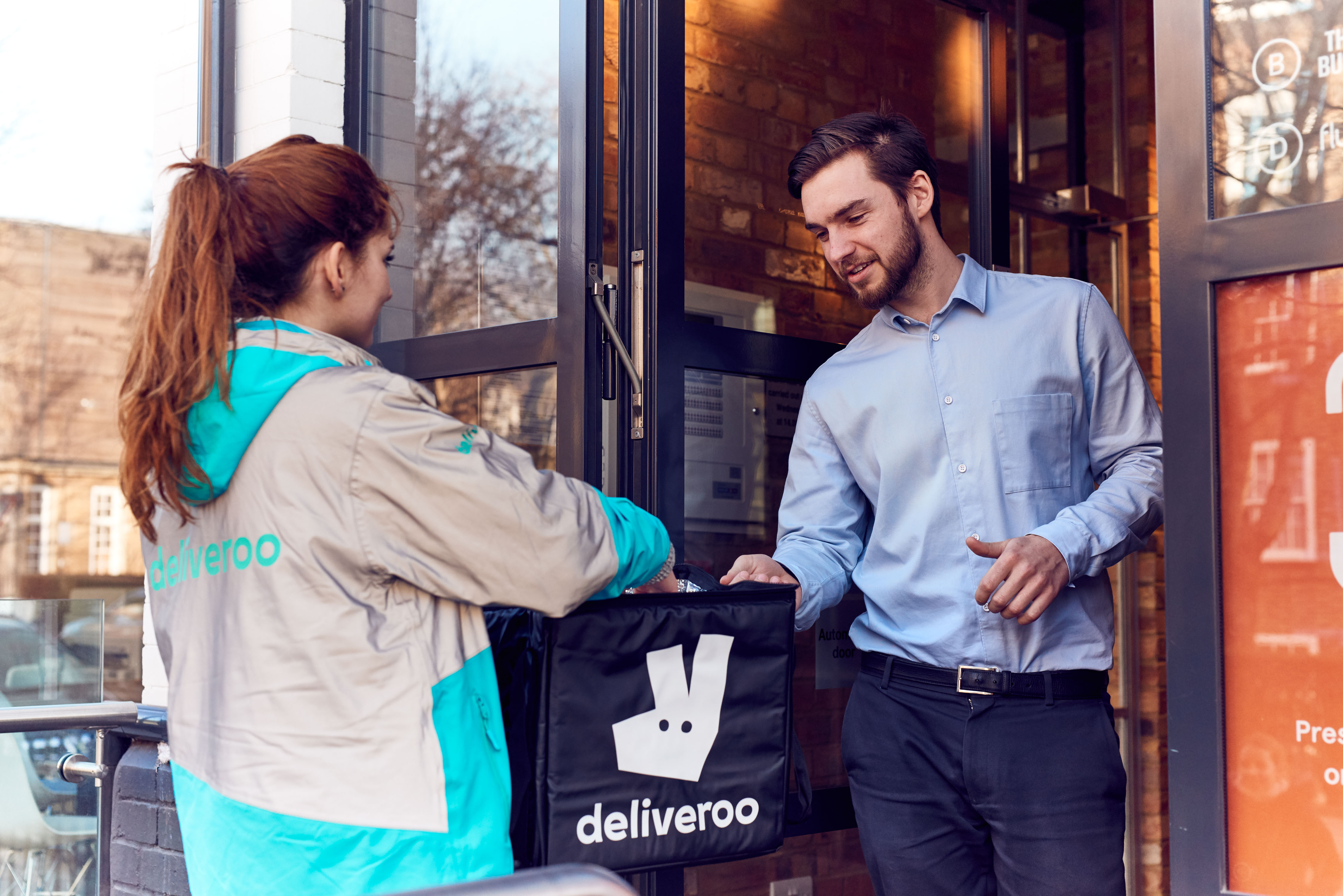 A Deliveroo driver delivers food to a customer, as the restaurant delivery company struggles with hacking