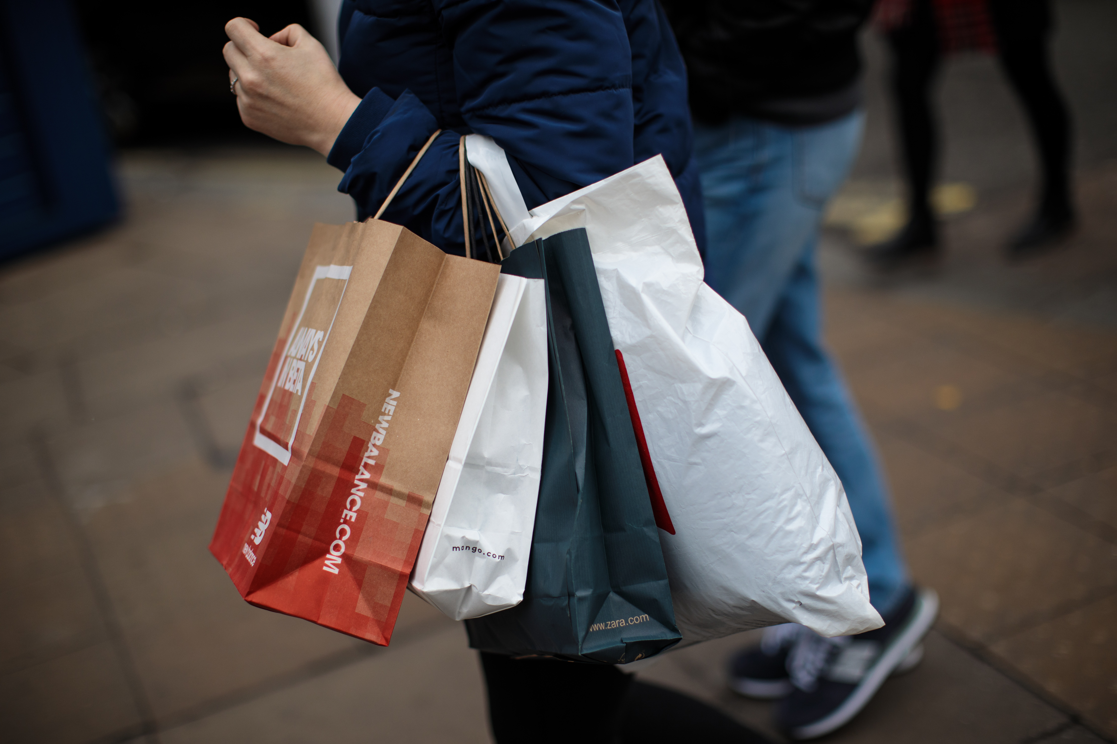 A person carries four shopping bags on their arm.