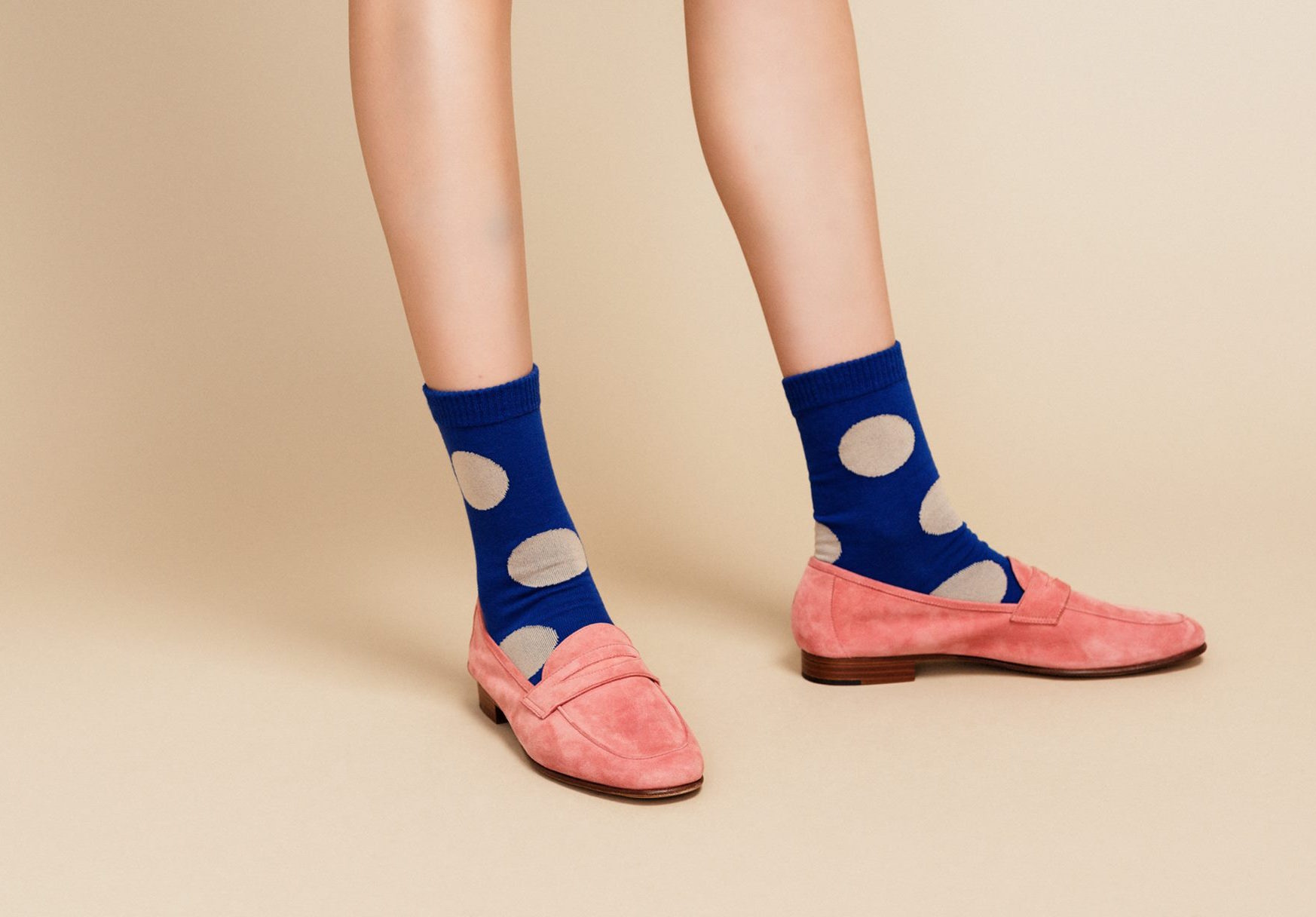 A model wearing polka dot socks and pink loafers