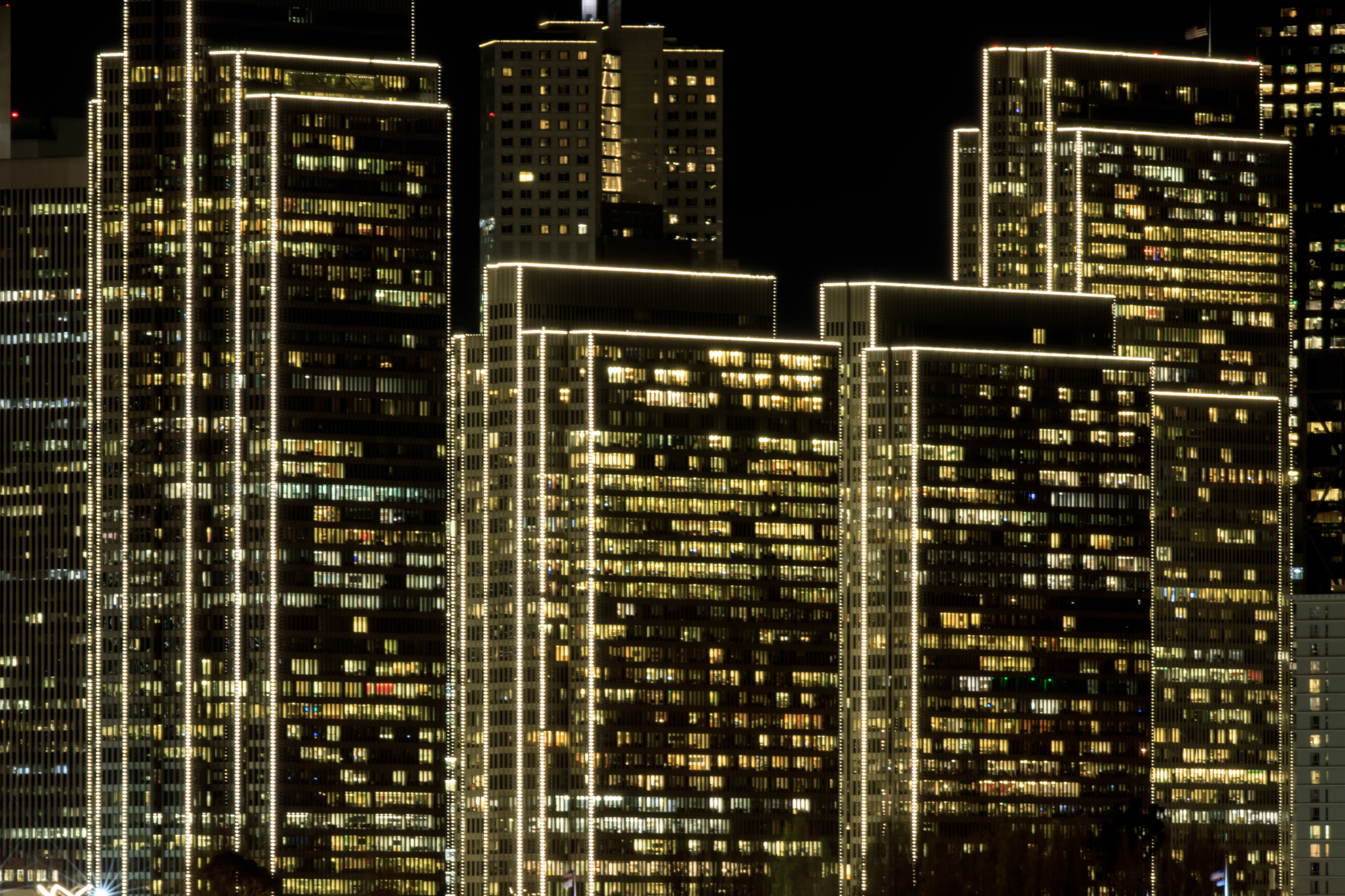 Tall rectangular buildings at night with white lights going up and down the sides of the buildings.