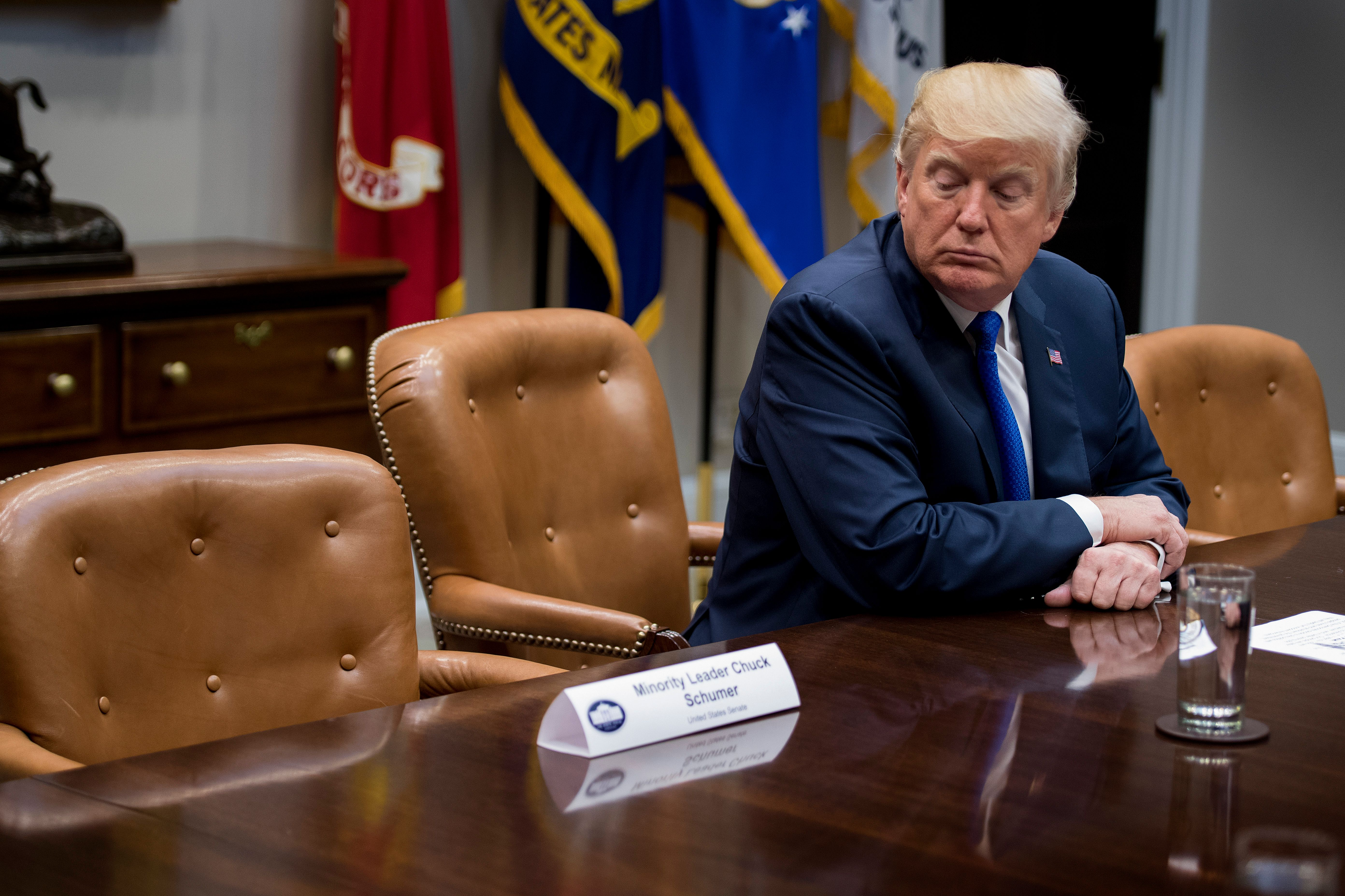 U.S. President Donald Trump looks at the empty chair of Senate Minority Leader Chuck Schumer (D-NY), after Schumer cancelled their meeting at the White House in Washington, D.C., on November 28, 2017.