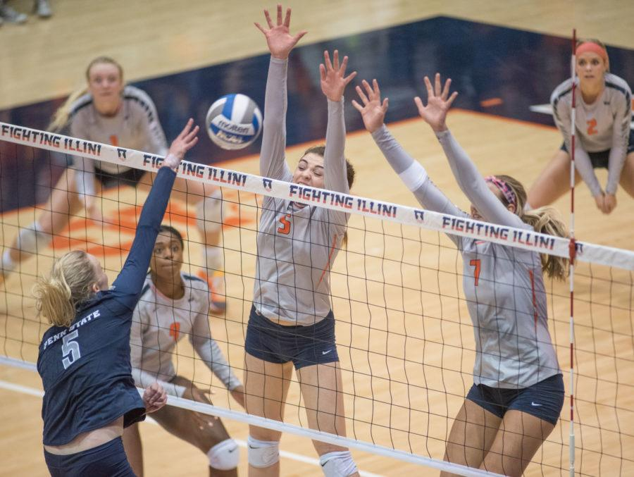 Ali Bastianelli (5) and Jocelynn Birks (7) attempt to block a Penn State spike in Friday's game at Huff Hall. Illinois lost 1-3.