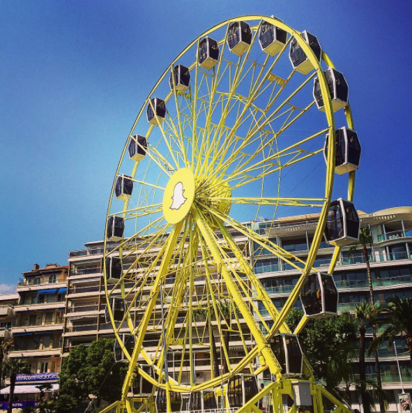 a Snapchat-themed ferris wheel in front of a hotel