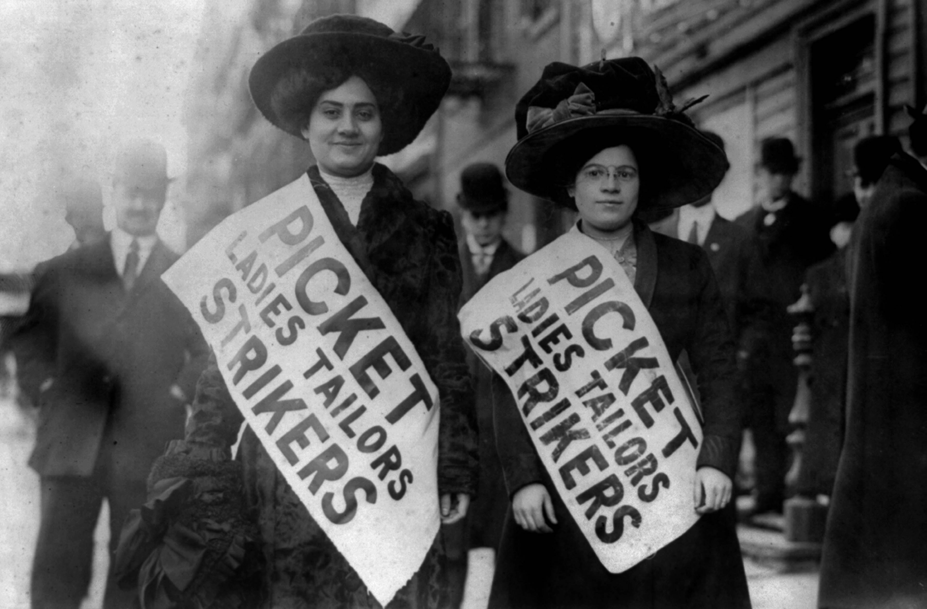 Two women in big hats in 1910 protesting working conditions