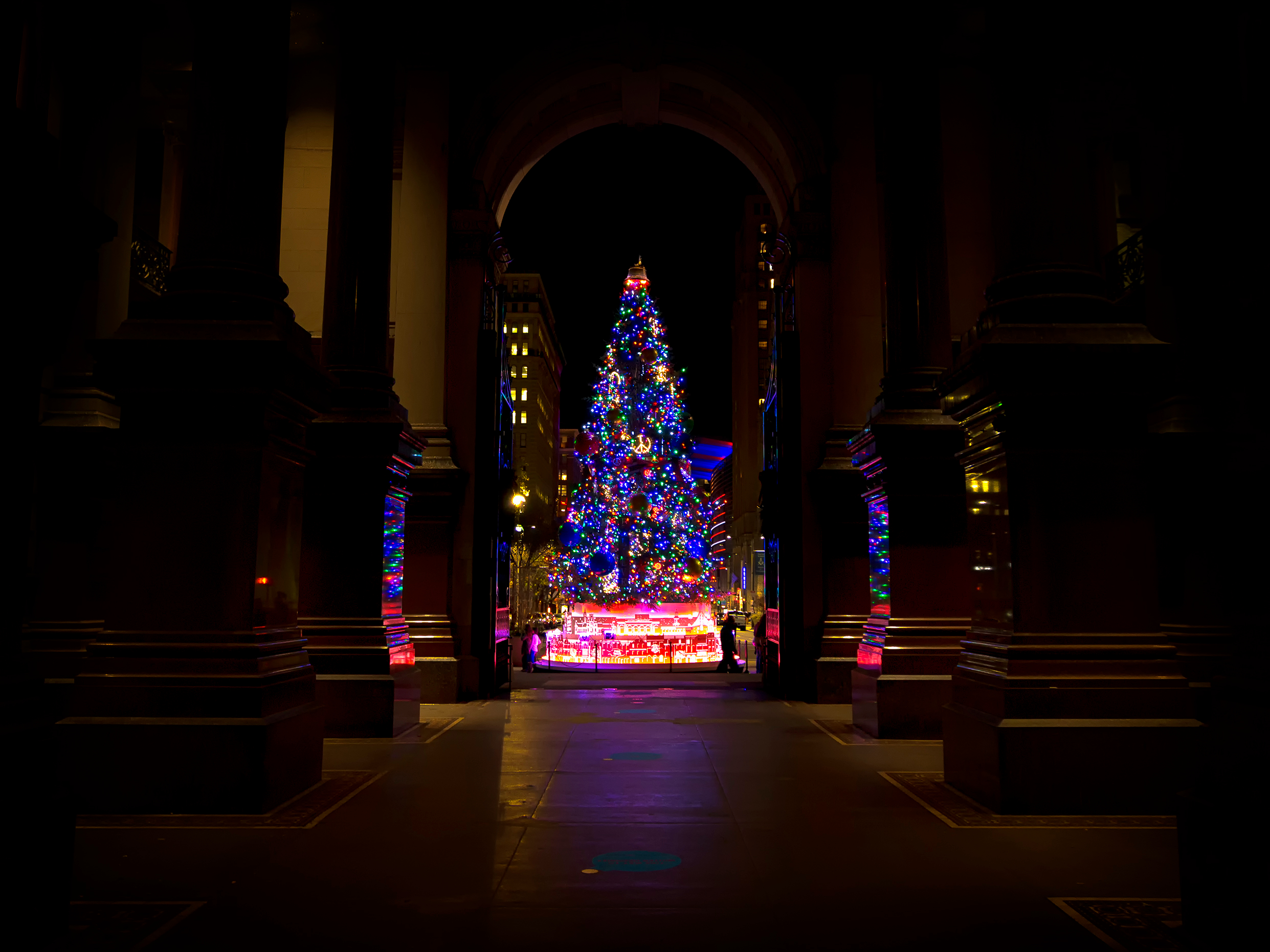 A Christmas tree illuminated with lights in a darkened room with arched doorways.