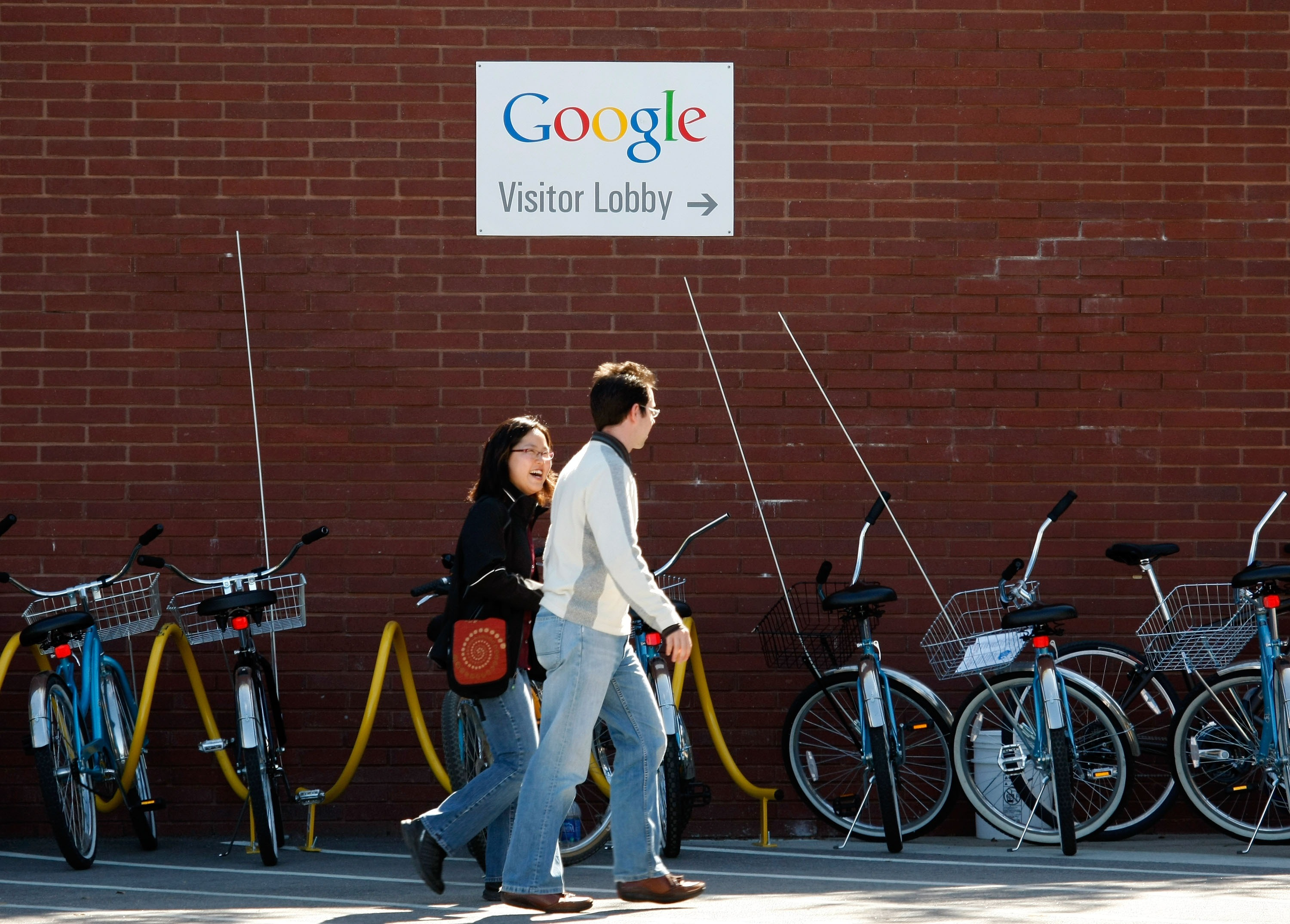 Google employees walk by a row of communal bicycles at the company's headquarters